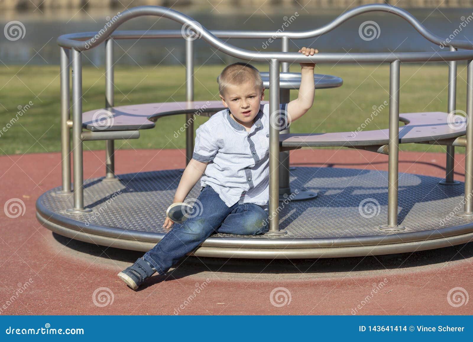 Pys på en lekplats Barn som utomhus spelar i sommar Ungelek på skolgård Lycklig unge i dagis eller förträning