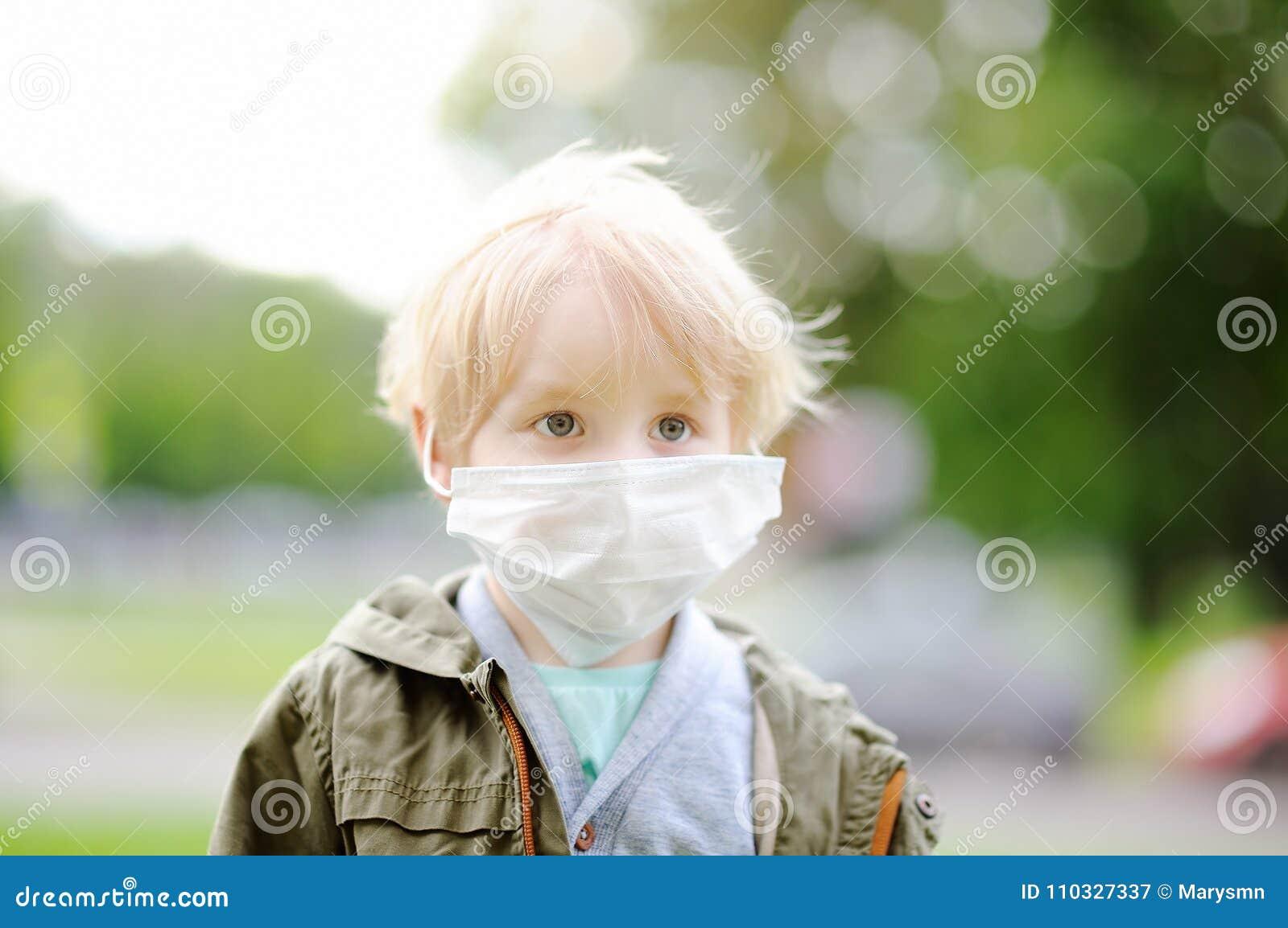 Pys som bär den medicinska framsidamaskeringen som skydd mot smittsamma sjukdomar