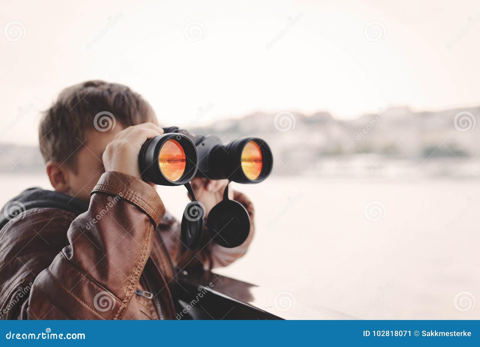 Pys som håller ögonen på och att se, stirra som söker för vid binokulärt