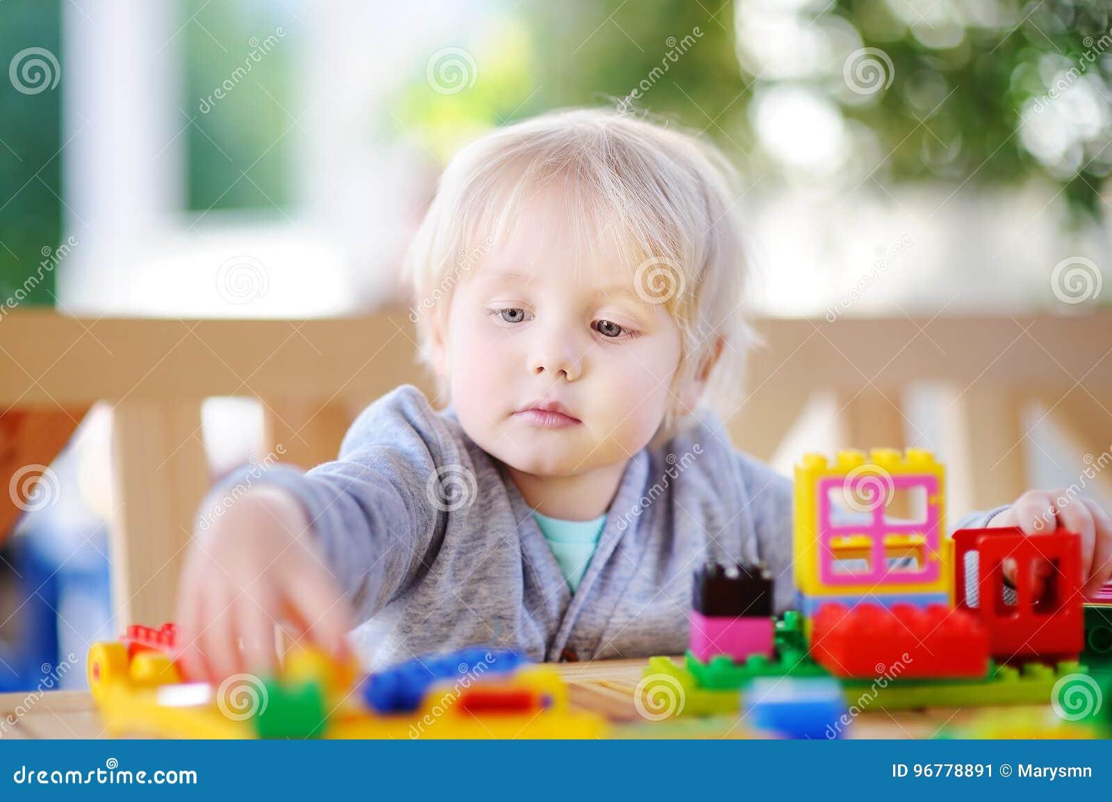 Pys som spelar med färgrika plast- kvarter på dagiset