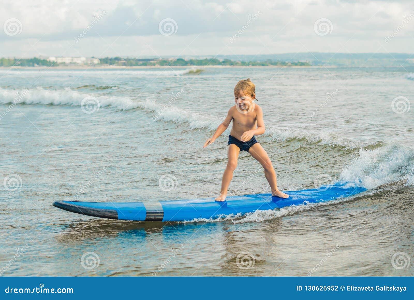 Pys som surfar på den tropiska stranden Barn på bränningbräde på havvåg Aktiva vattensportar för ungar Ungesimning med
