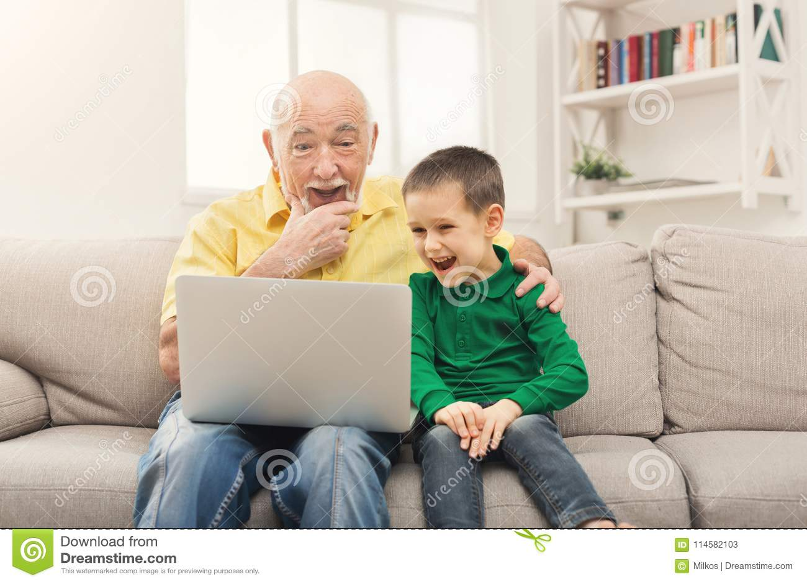 Pys som undervisar hans farfar att använda bärbara datorn