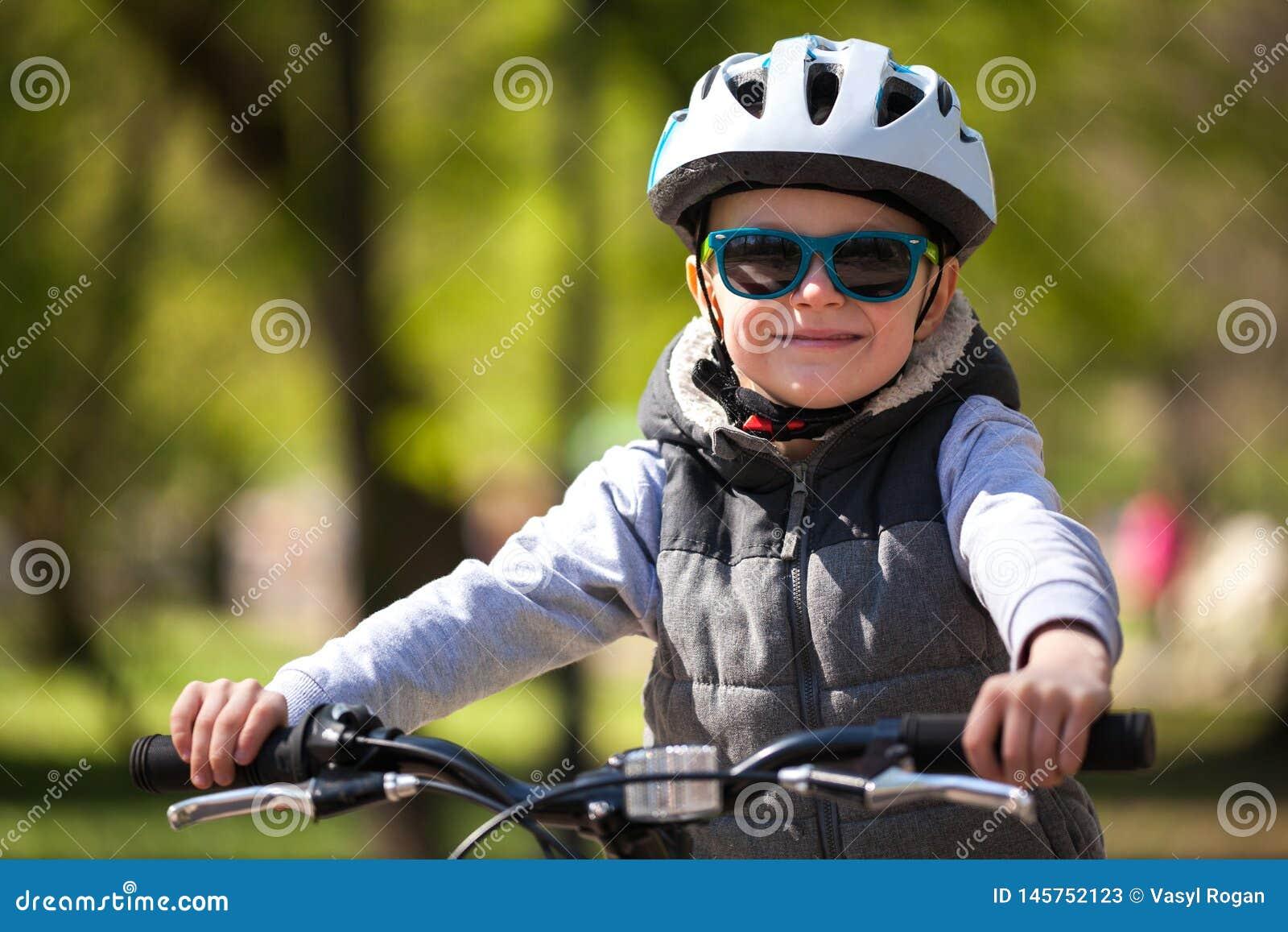 Pysen l?r att rida en cykel i parkerar Den gulliga pojken i solglas?gon rider en cykel Lyckligt le barn i hj?lm som rider cykla