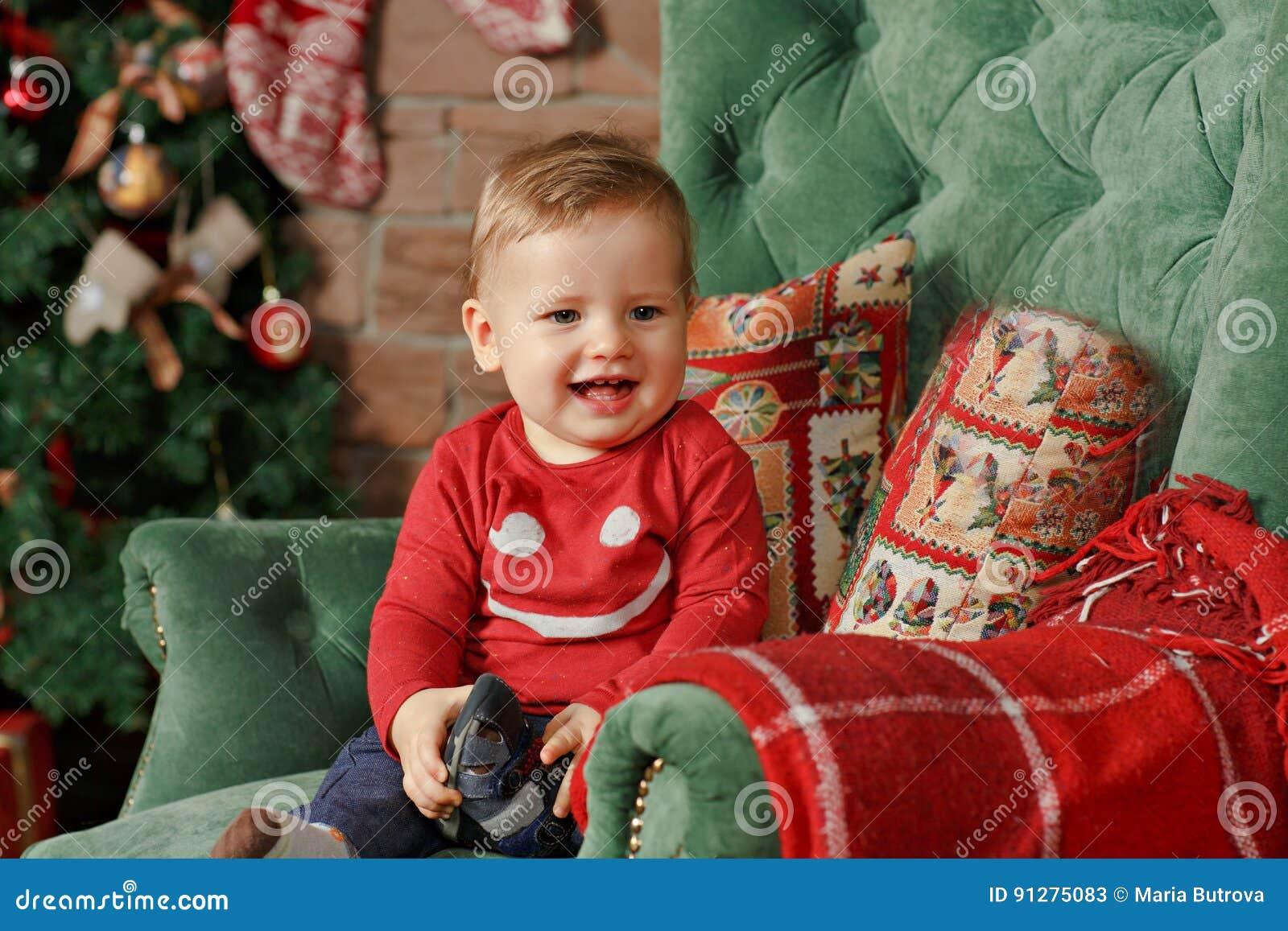 Pysen med litet paraplykinder ler på jul Inre