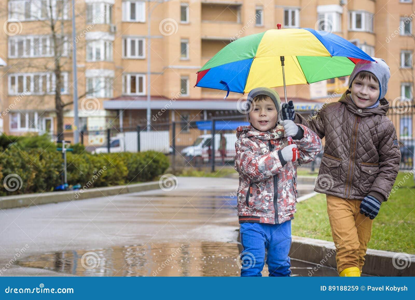 Pysen som spelar i regnig sommar, parkerar Barn med det färgrika regnbågeparaplyet, det vattentäta laget och kängor som hoppar i