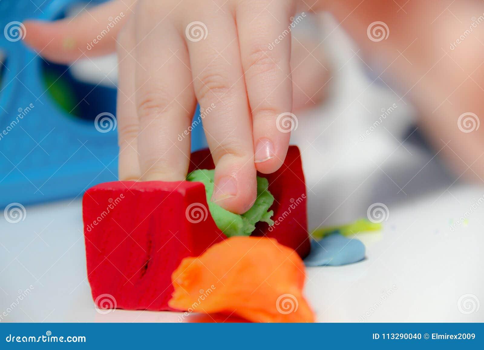 Pysen tre gamla år sitter på tabellen och spelar med plasticine och trä- och plast- leksaker, kuber och tärning