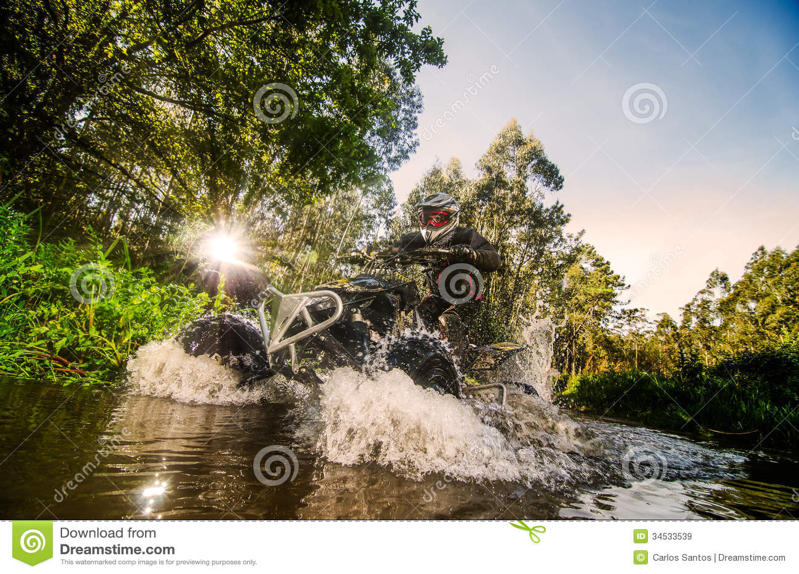 Quad rider through water stream