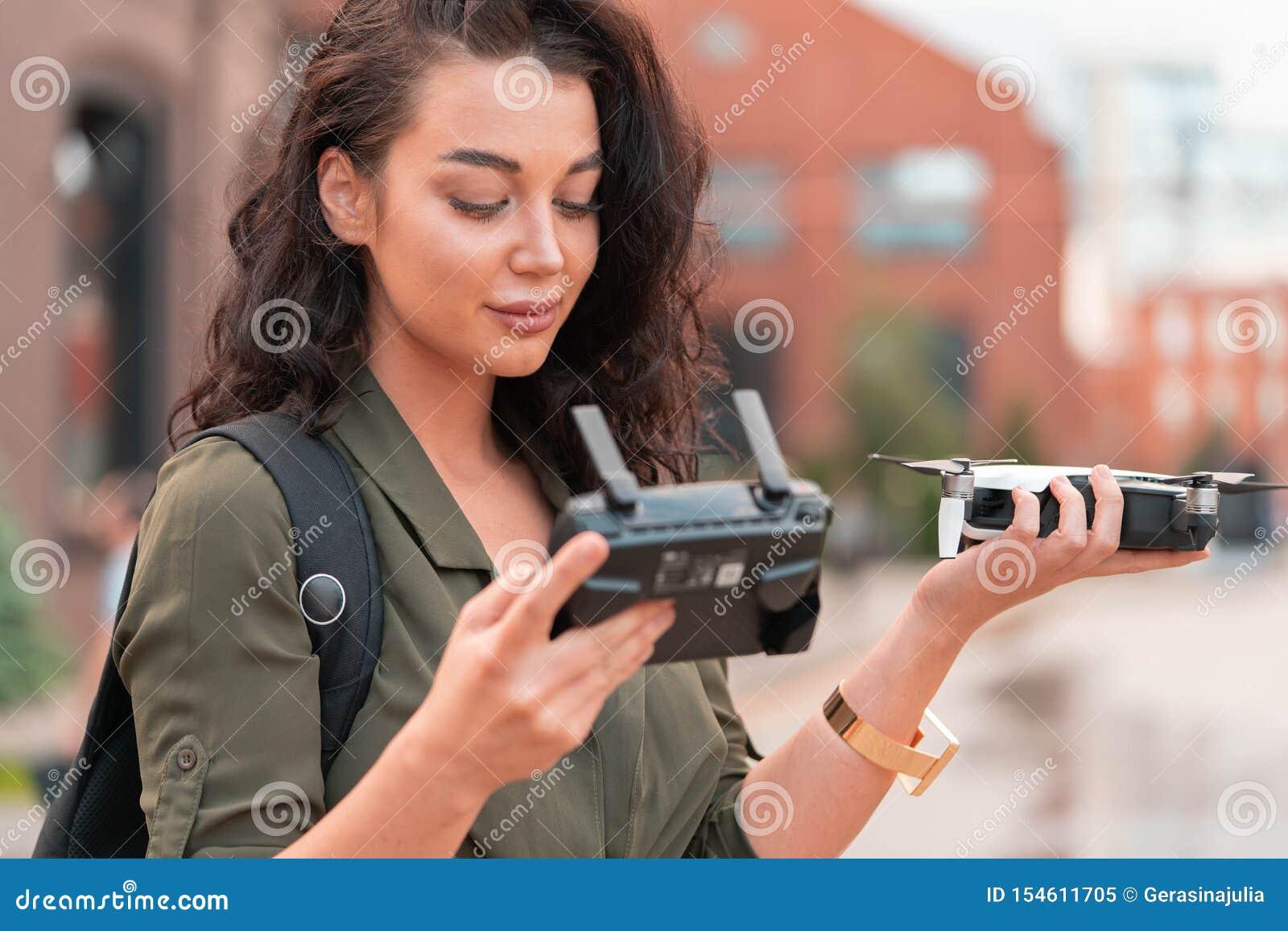 Quadcopter de lancement de bourdon de jeune belle femme au fond urbain