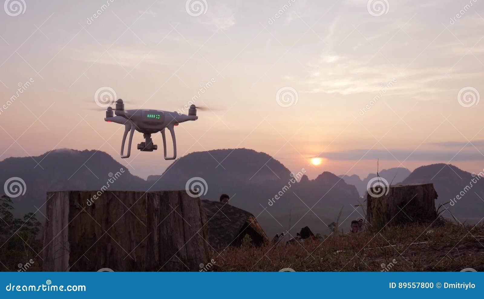 Quadcopter-Drohne, das im Park bei schönem Sonnenaufgang mit Bergen auf Hintergrund sich entfernt Phangnga, Thailand stock footage