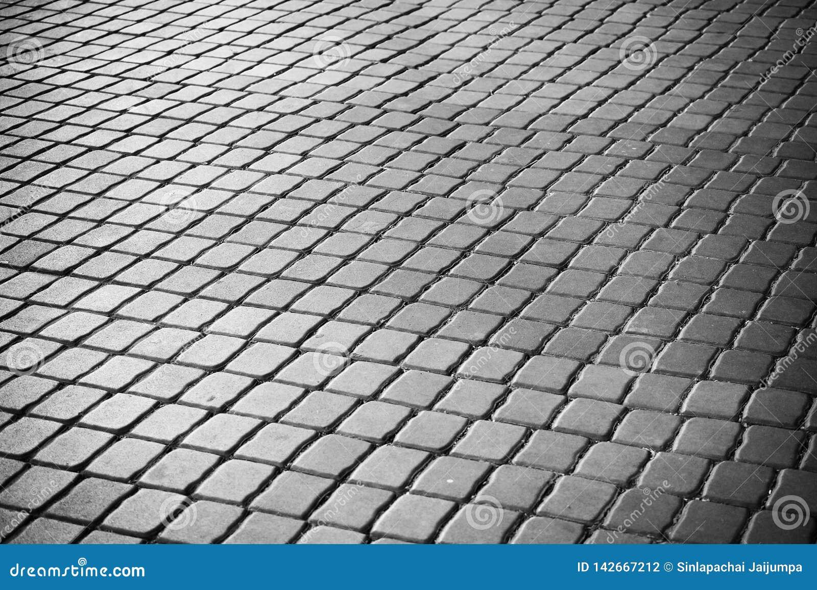 Quadratischer Gehweg des Mörserblogs Schwarzweiss vom abstrakten Hintergrund Minimalismus architecrure Details des modernen Muste