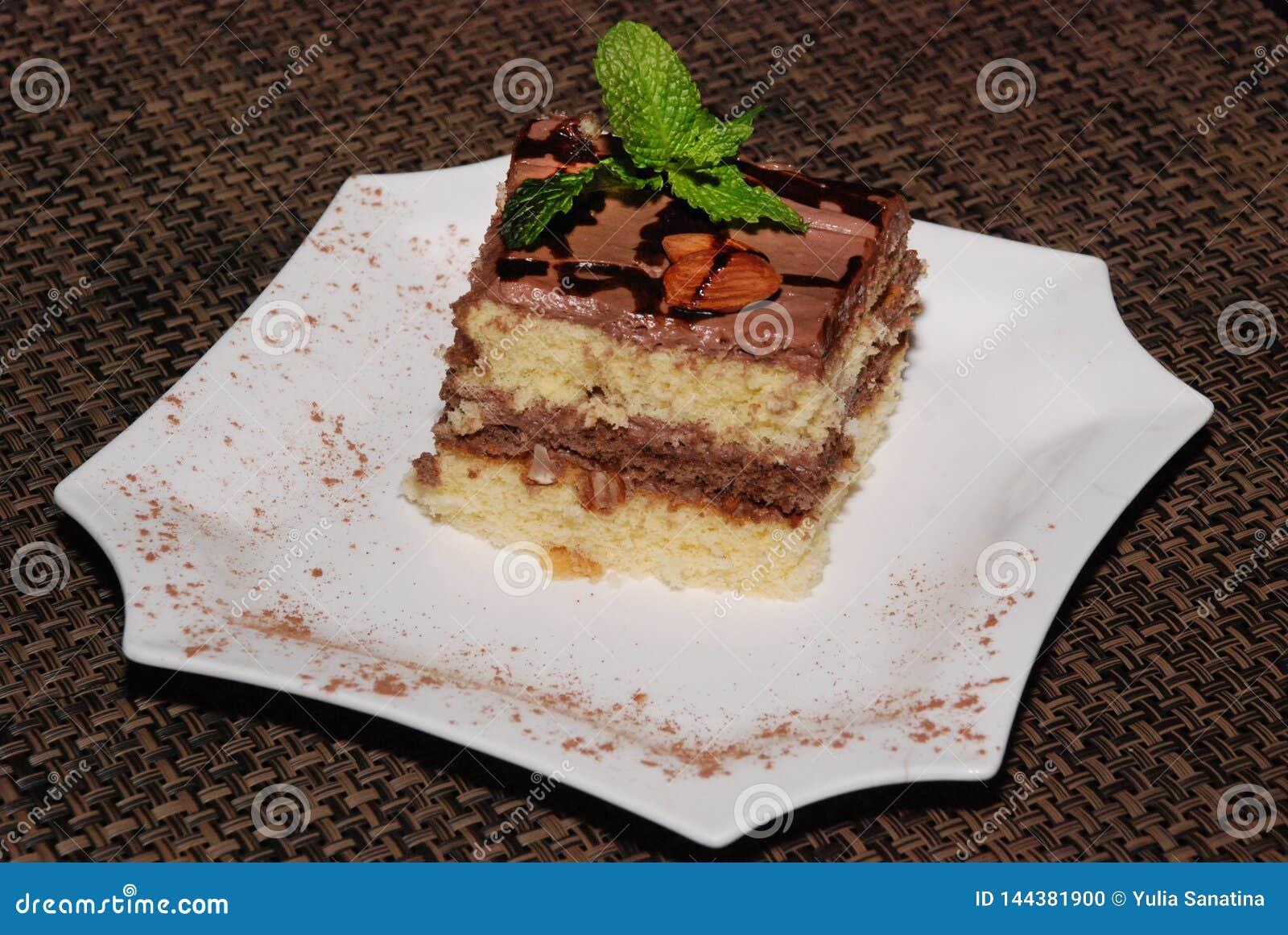 Quadratisches Stück des Kuchens mit Schokolade und Mandel auf der weißen Platte