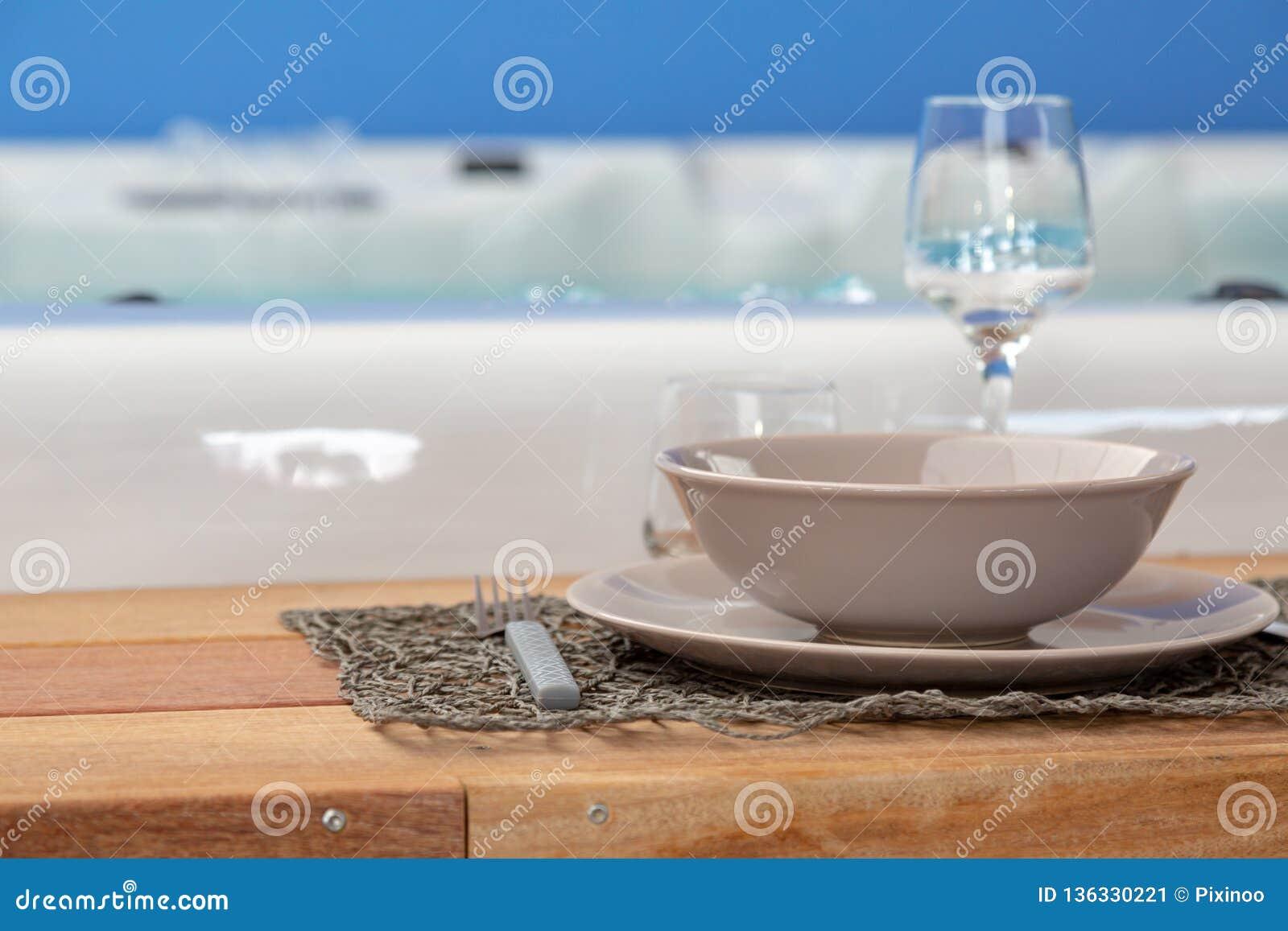 Quadro de madeira em torno de um Jacuzzi com faqueiro para jantares luxuosos