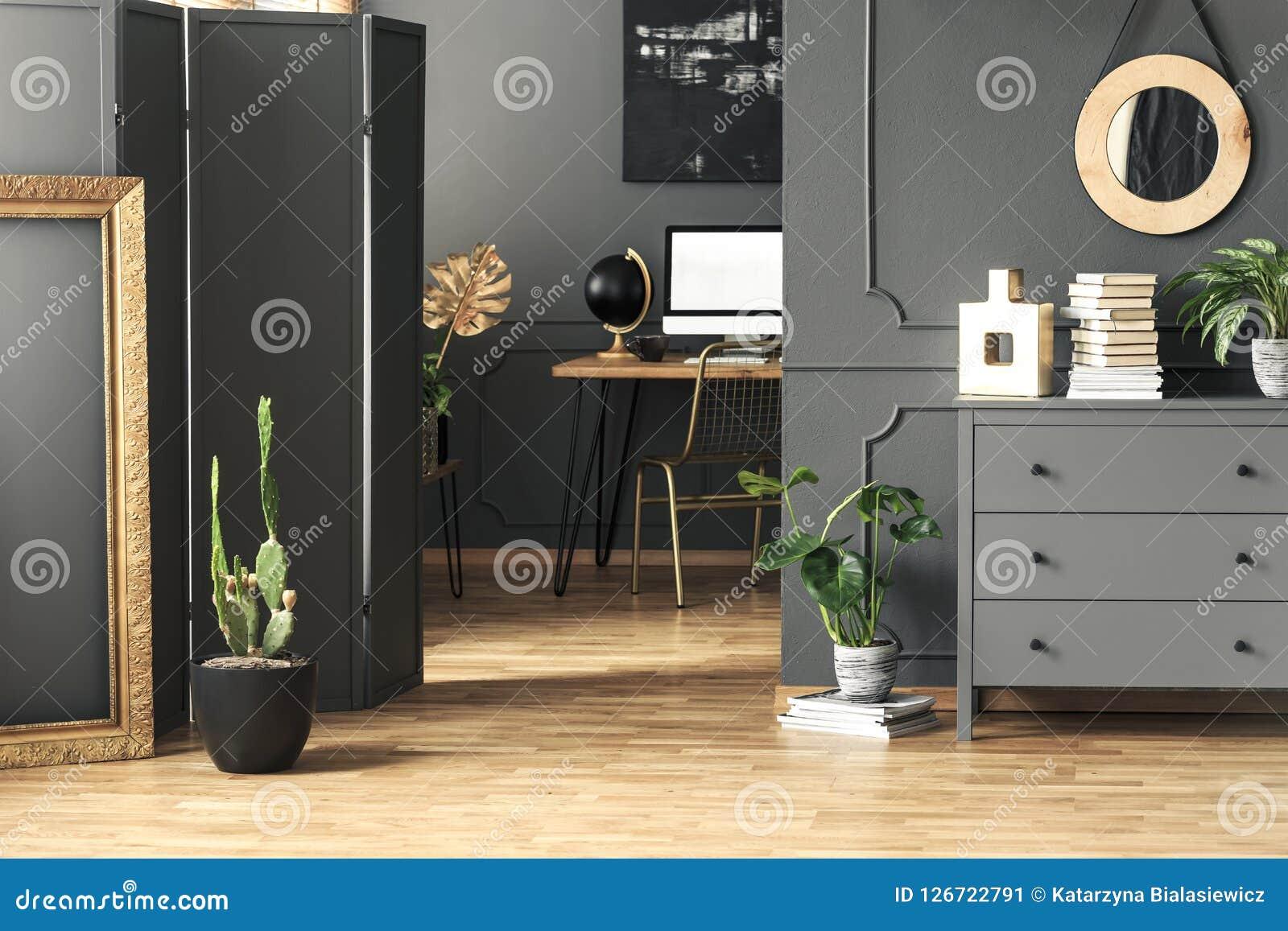 Quadro do ouro ao lado do cacto no interior cinzento do espaço de trabalho com o espelho redondo acima do armário Foto real