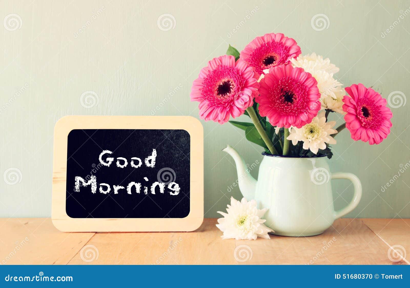 Quadro-negro com o bom dia da frase escrito nele ao lado do vaso com flores frescas