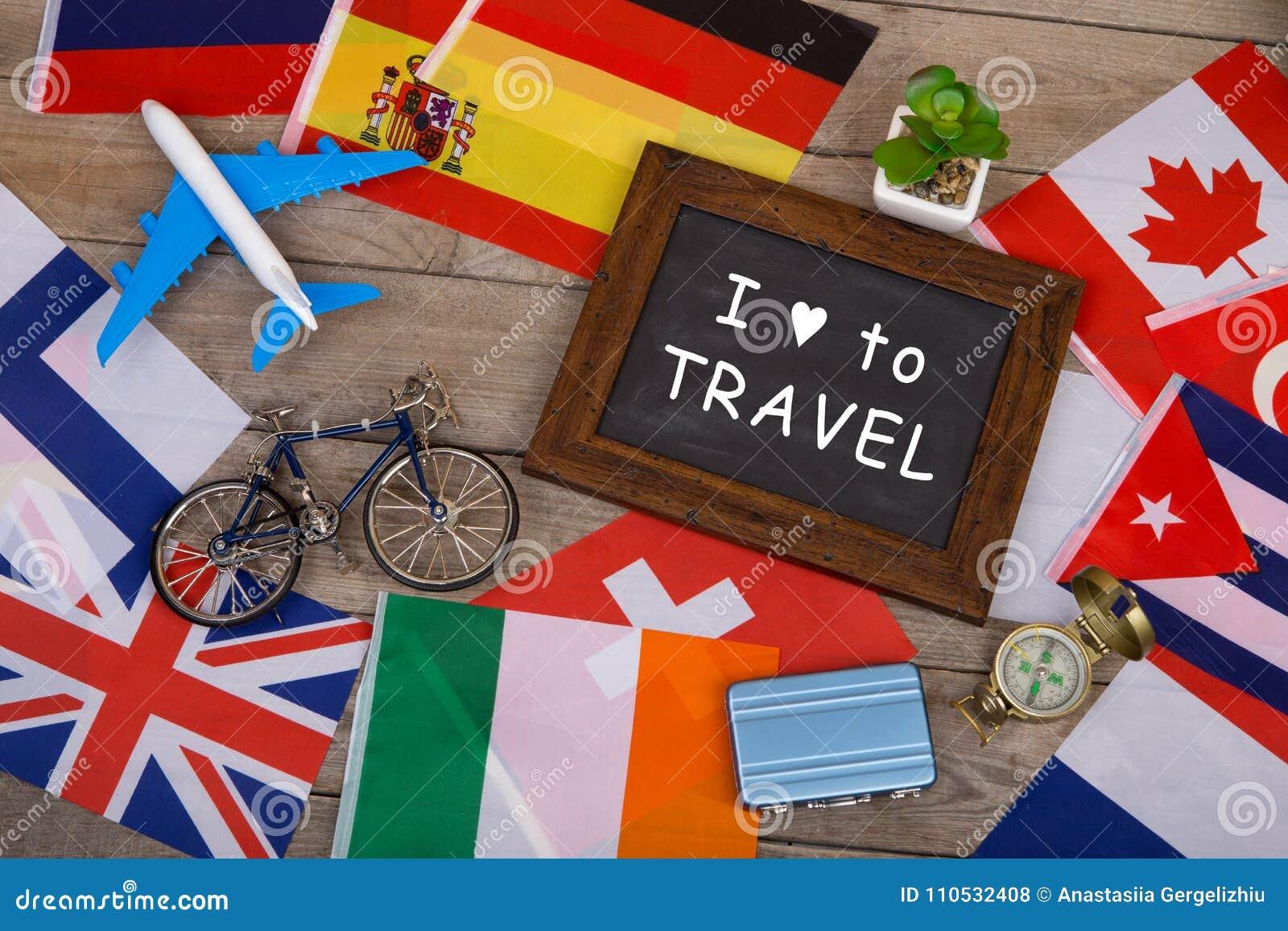 Quadro-negro com texto & x22; Eu amo a Travel& x22; , bandeiras de países diferentes, modelo do avião, pouca bicicleta e mala de