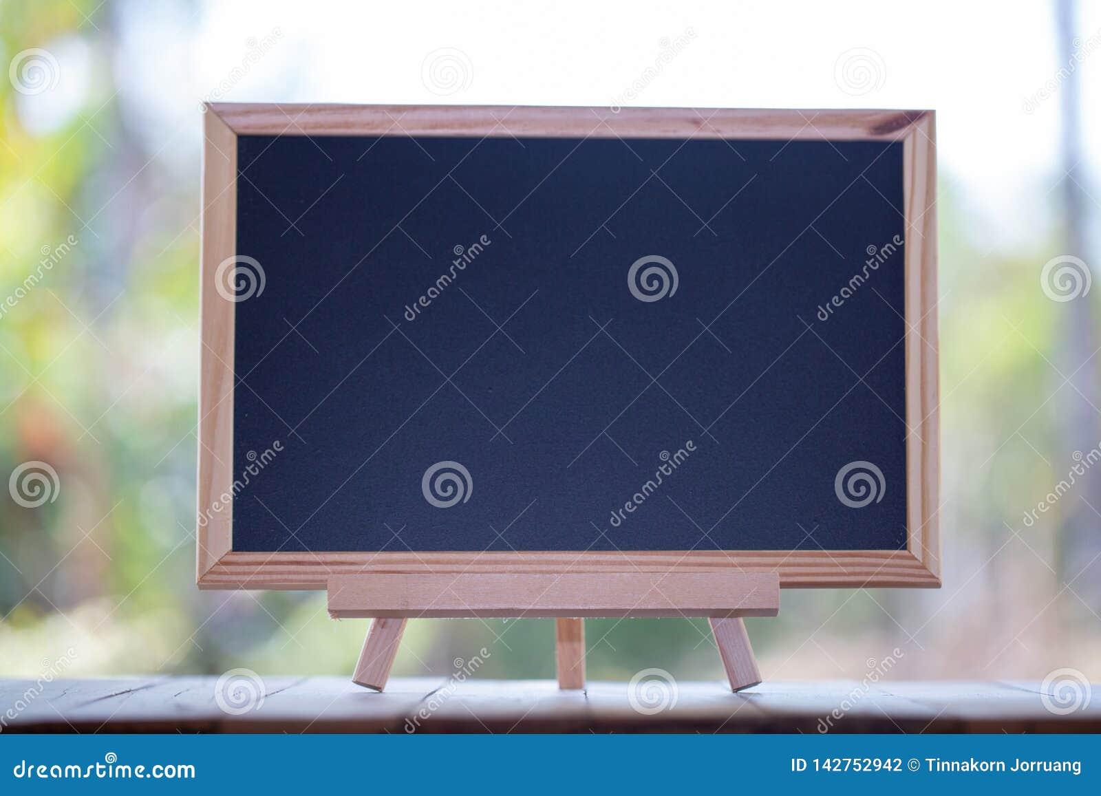 Quadro-negro de Mini Blank na tabela de madeira com espaço da cópia quadro