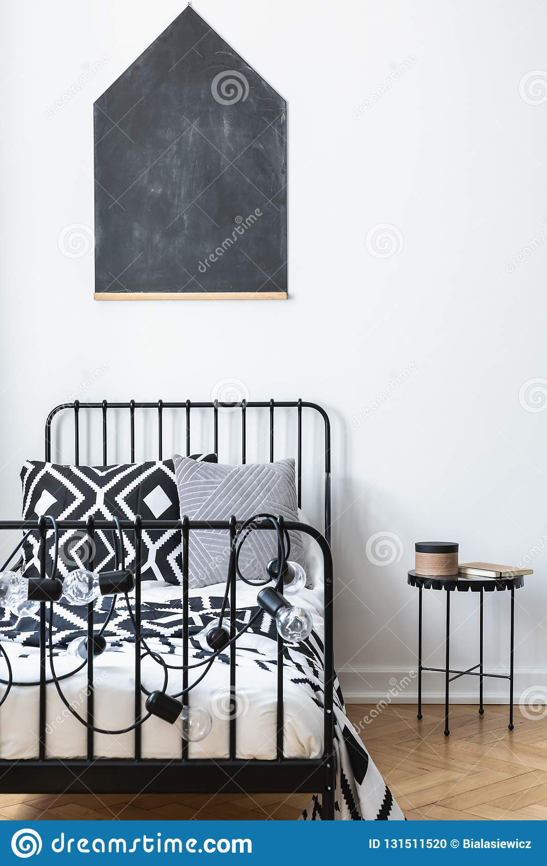 Quadro-negro na parede do quarto dos adolescentes com fundamento modelado preto e branco na única cama do metal, real