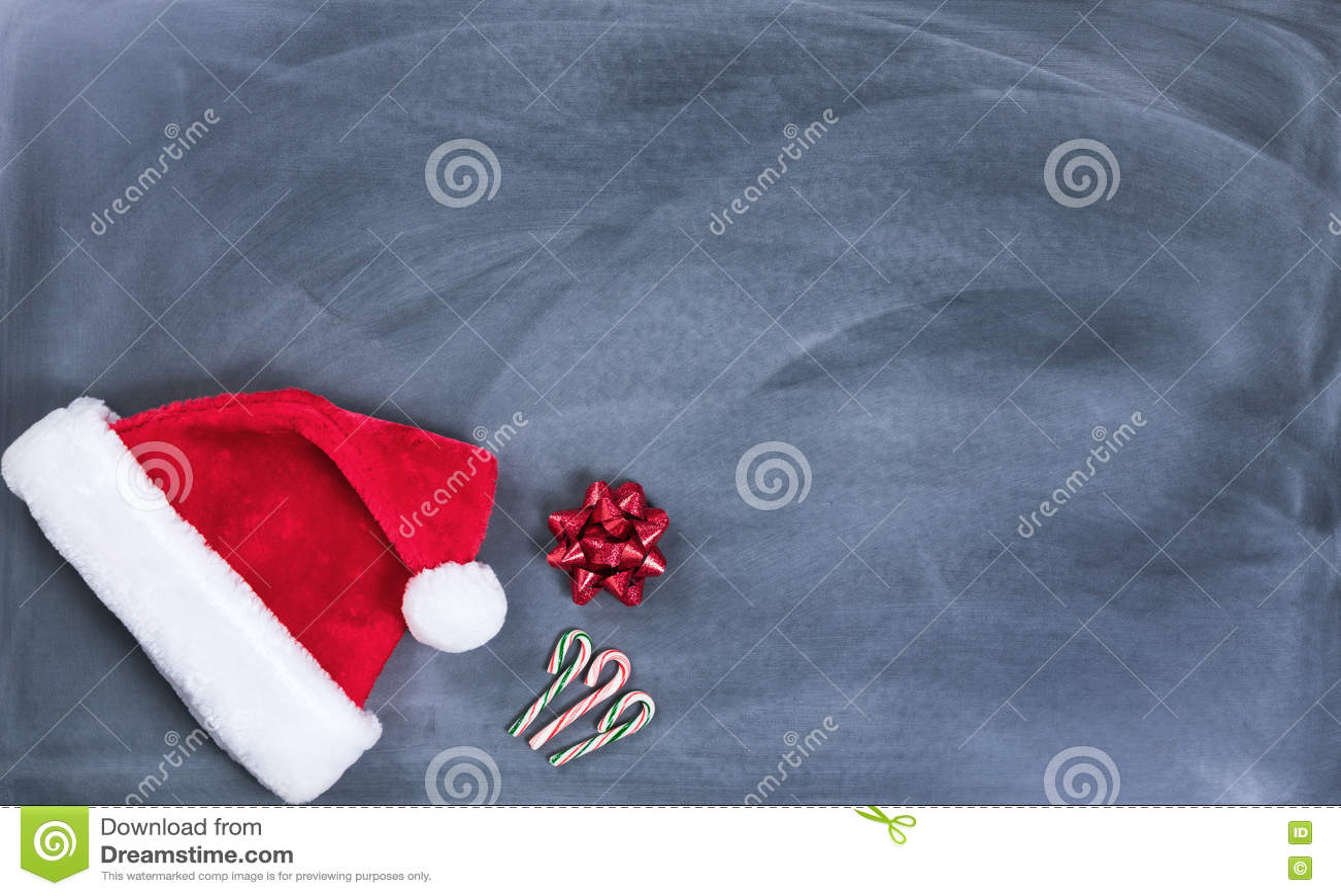 Quadro preto apagado com os bastões do tampão e de doces de Santa mais o presente
