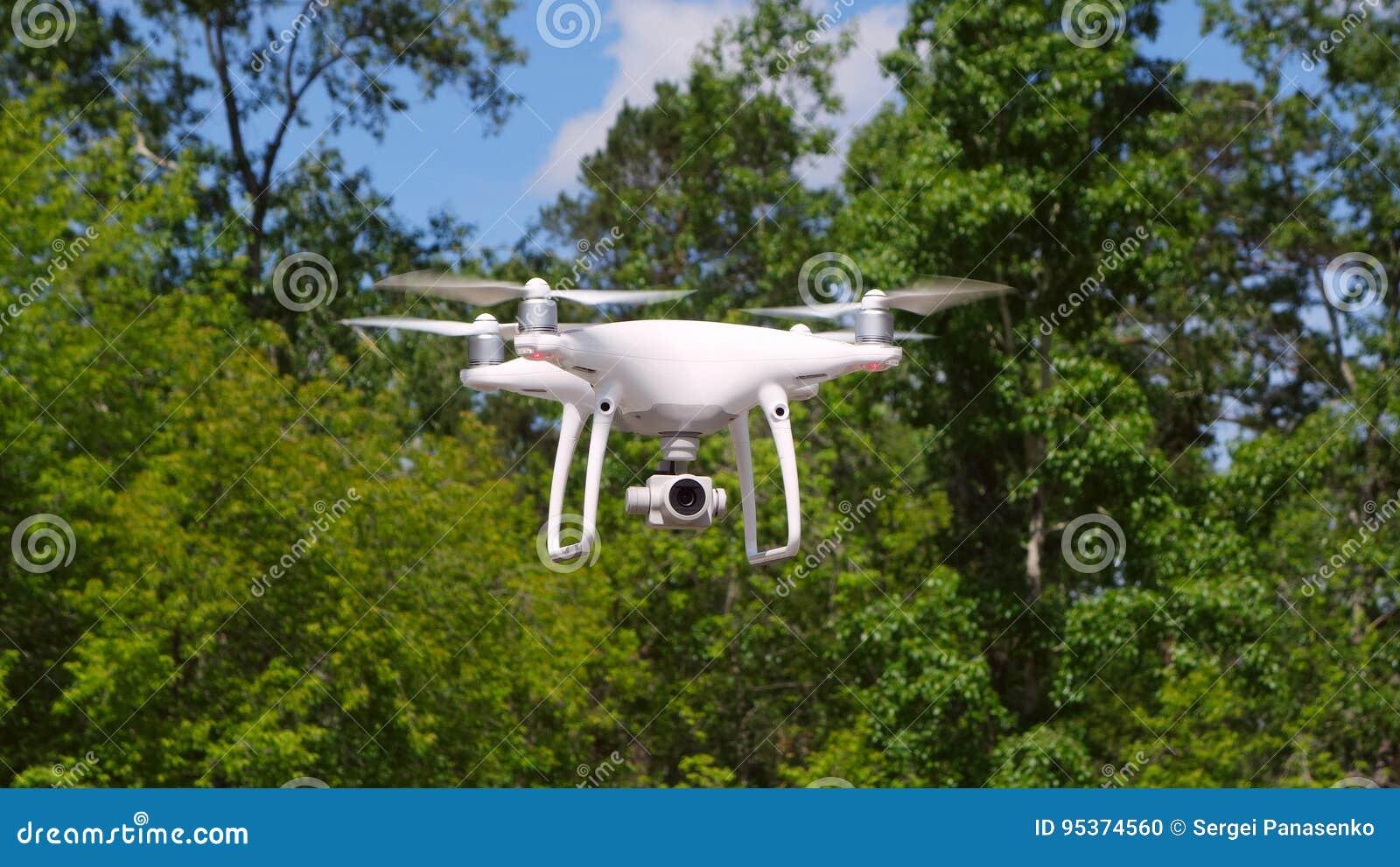 Quadrocopter-Brummen mit der Kamera Modernes RC-Brummen Hubschrauberfliegen gegen Grün unscharfen Hintergrund