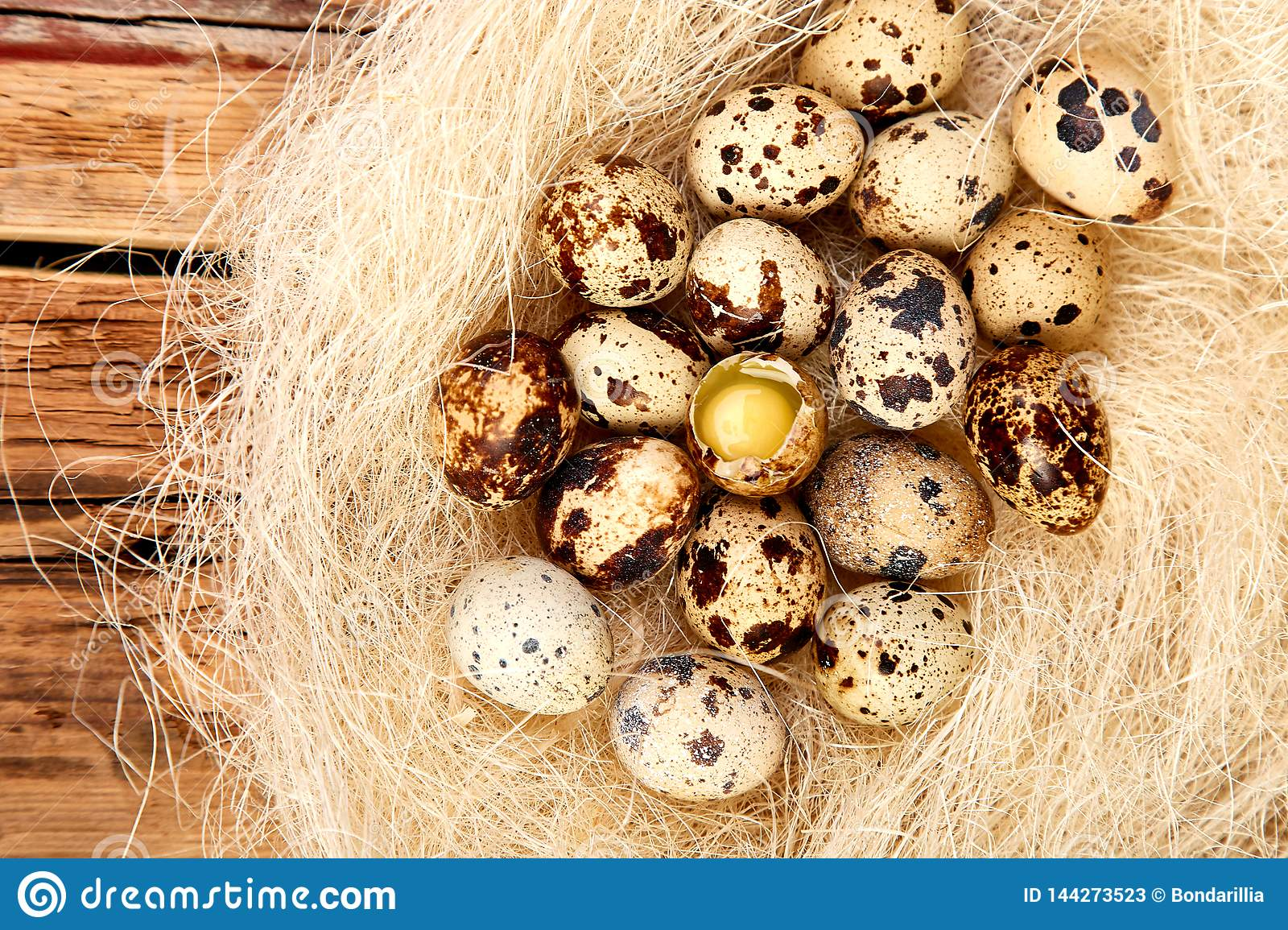 Quail  easter eggs in the nest on wooden background
