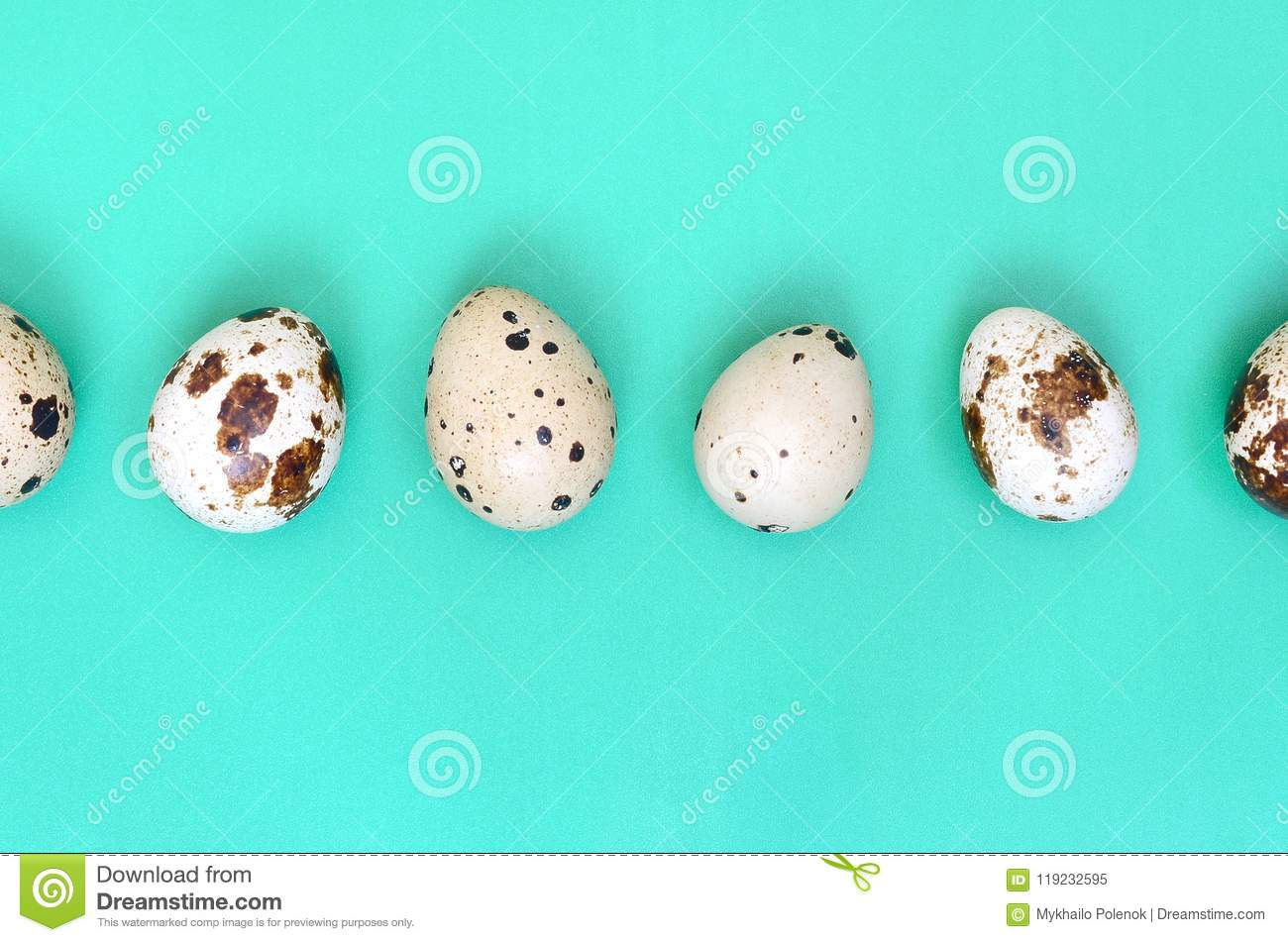 Quail eggs on a light green surface, top view, empty place for t