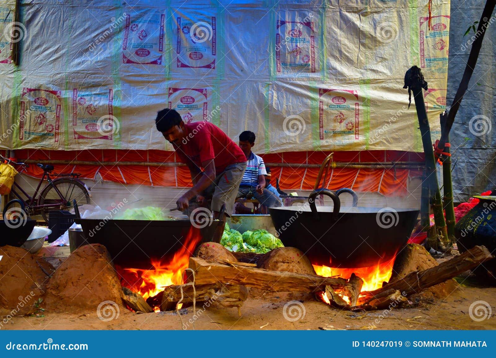 Qualche gente sta cucinando l alimento in una grande casseruola per la celebrazione della cerimonia di nozze