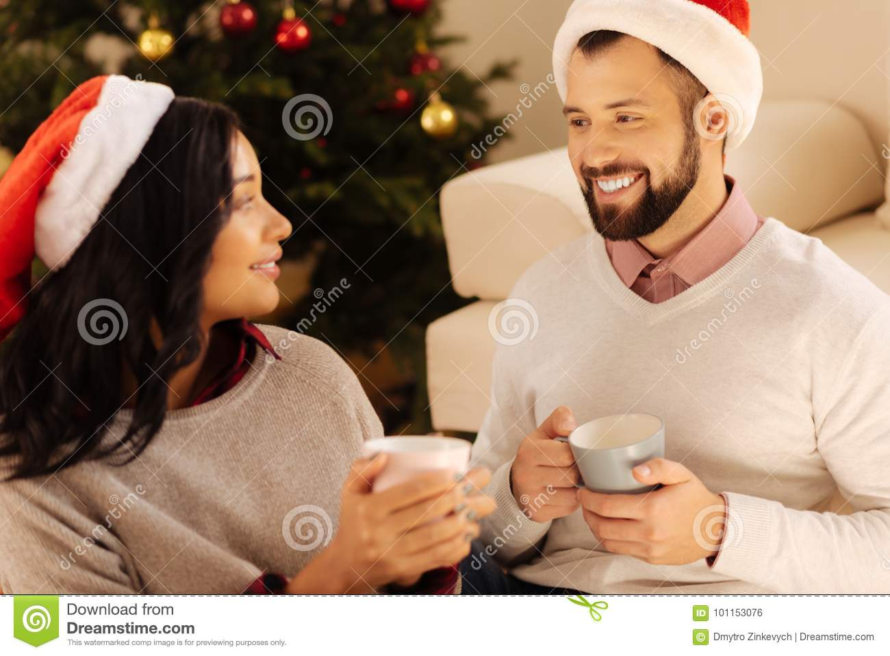 Happy couple drinking coffee together on Christmas Eve