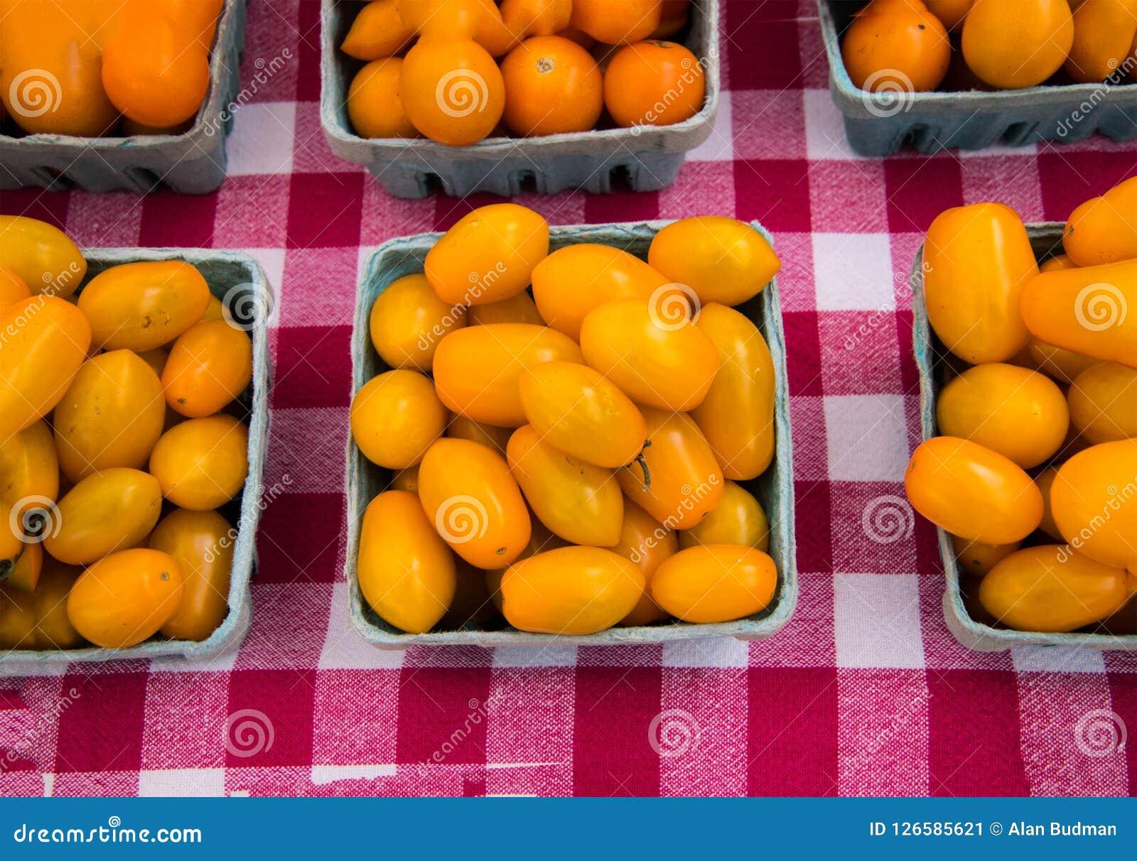 Quarti dei pomodori gialli ovali su una tovaglia rossa e bianca della scacchiera
