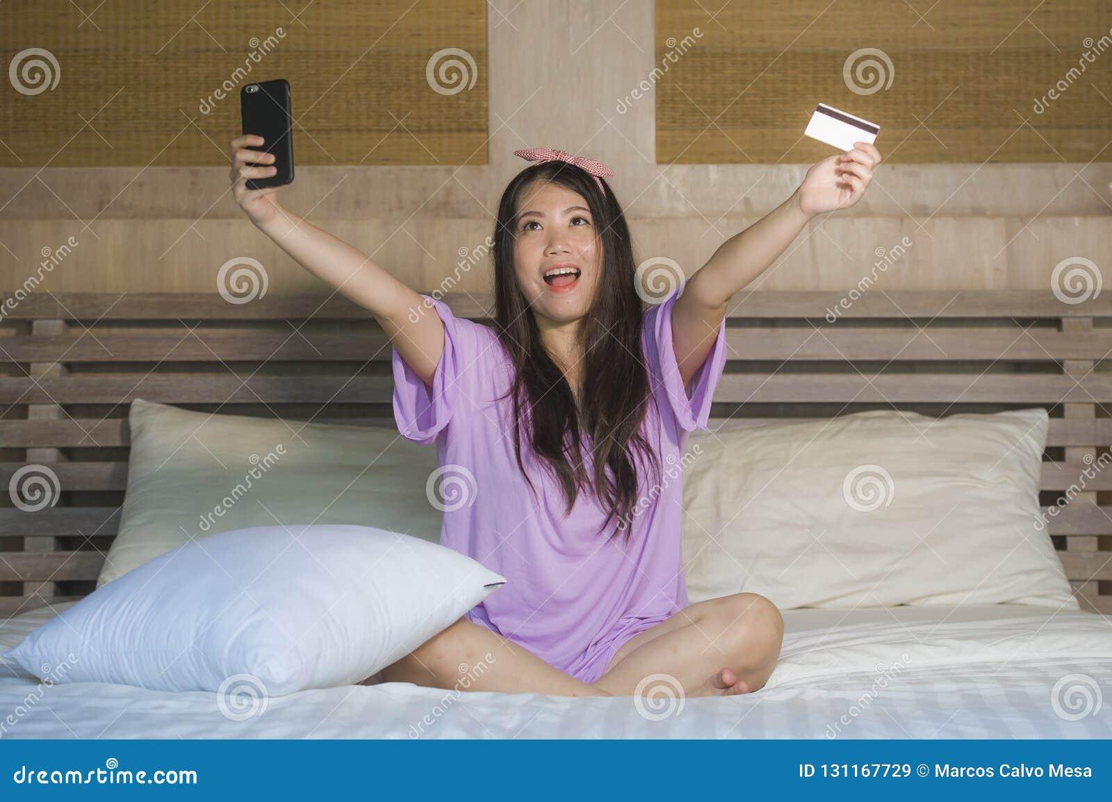 Quarto chinês asiático bonito e feliz novo da mulher em casa usando Internet banking do cartão de crédito com telefone celular no