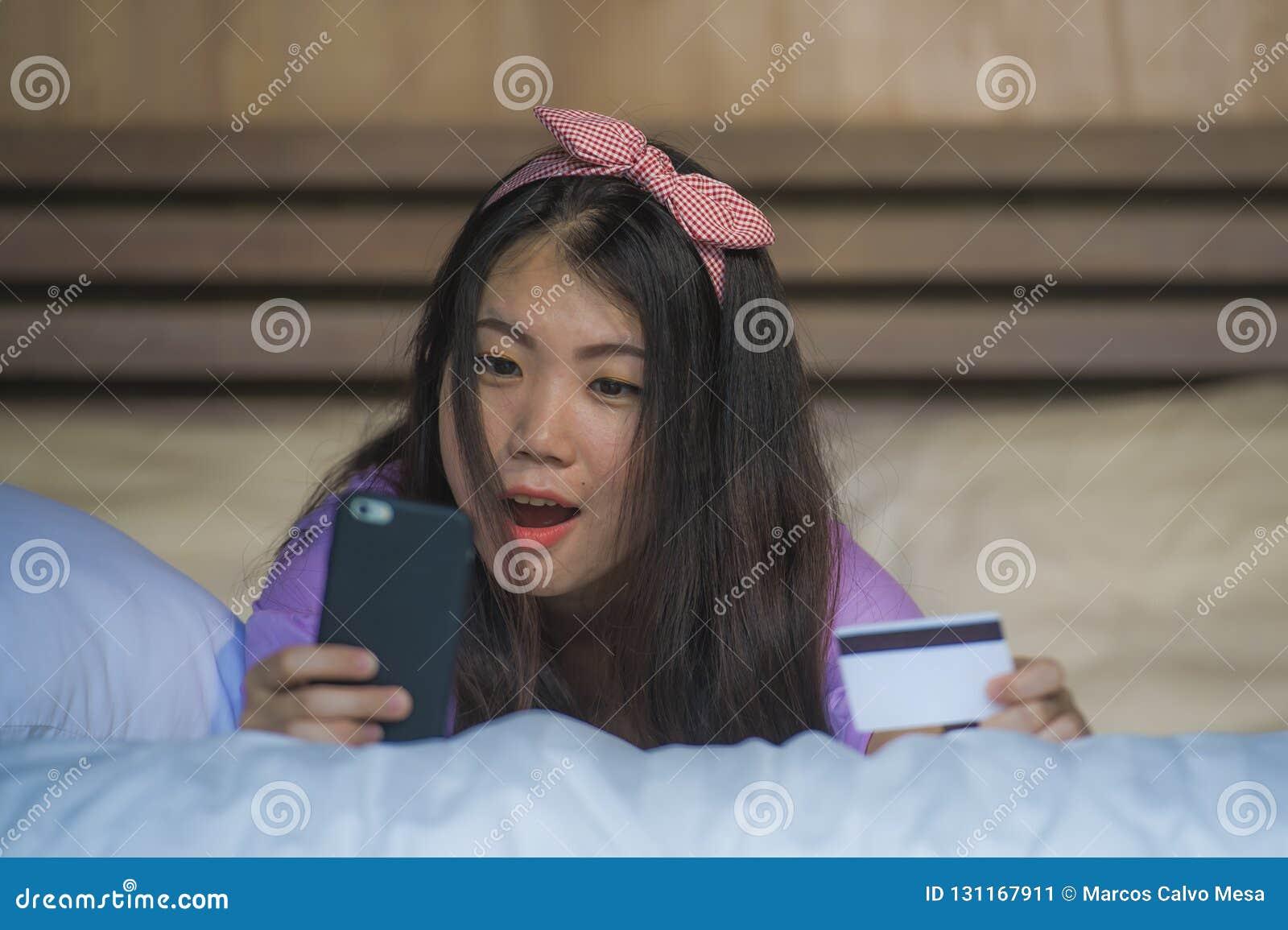 Quarto coreano asiático bonito e feliz novo da mulher em casa usando Internet banking do cartão de crédito com telefone celular n