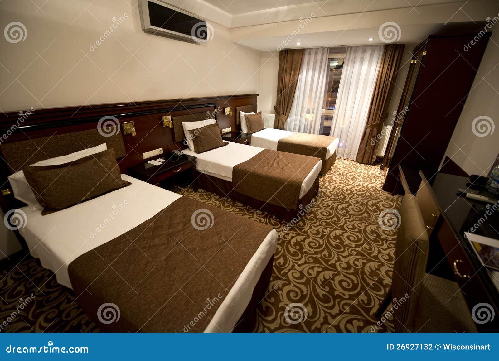 Quarto de hotel pequeno com as três únicas camas