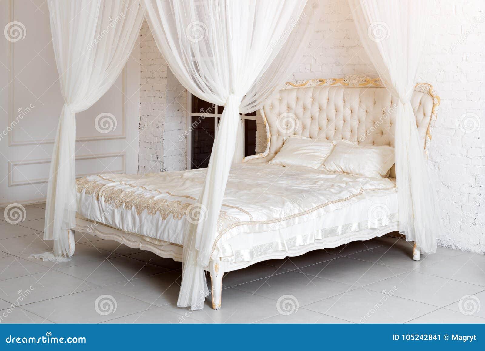Quarto em cores de luz suave Cama de casal confortável grande de quatro cartazes no quarto clássico elegante Branco elegante luxu
