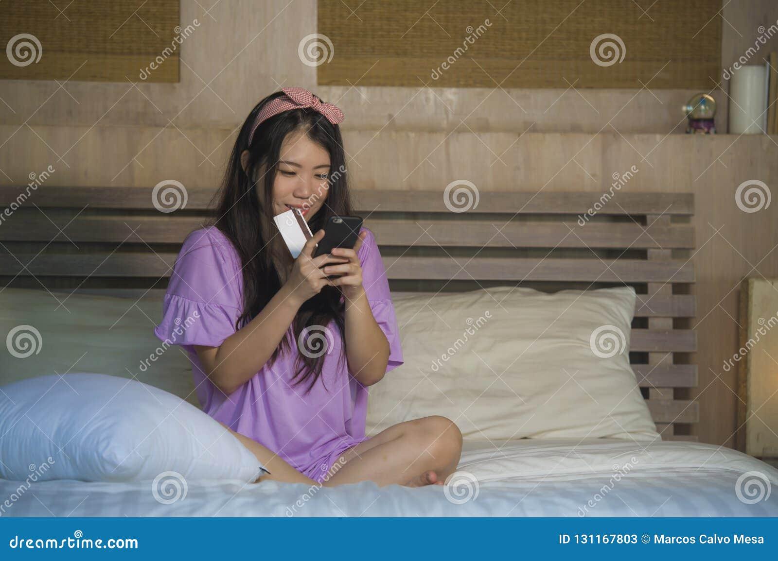 Quarto japonês asiático bonito e feliz novo da mulher em casa usando Internet banking do cartão de crédito com telefone celular n