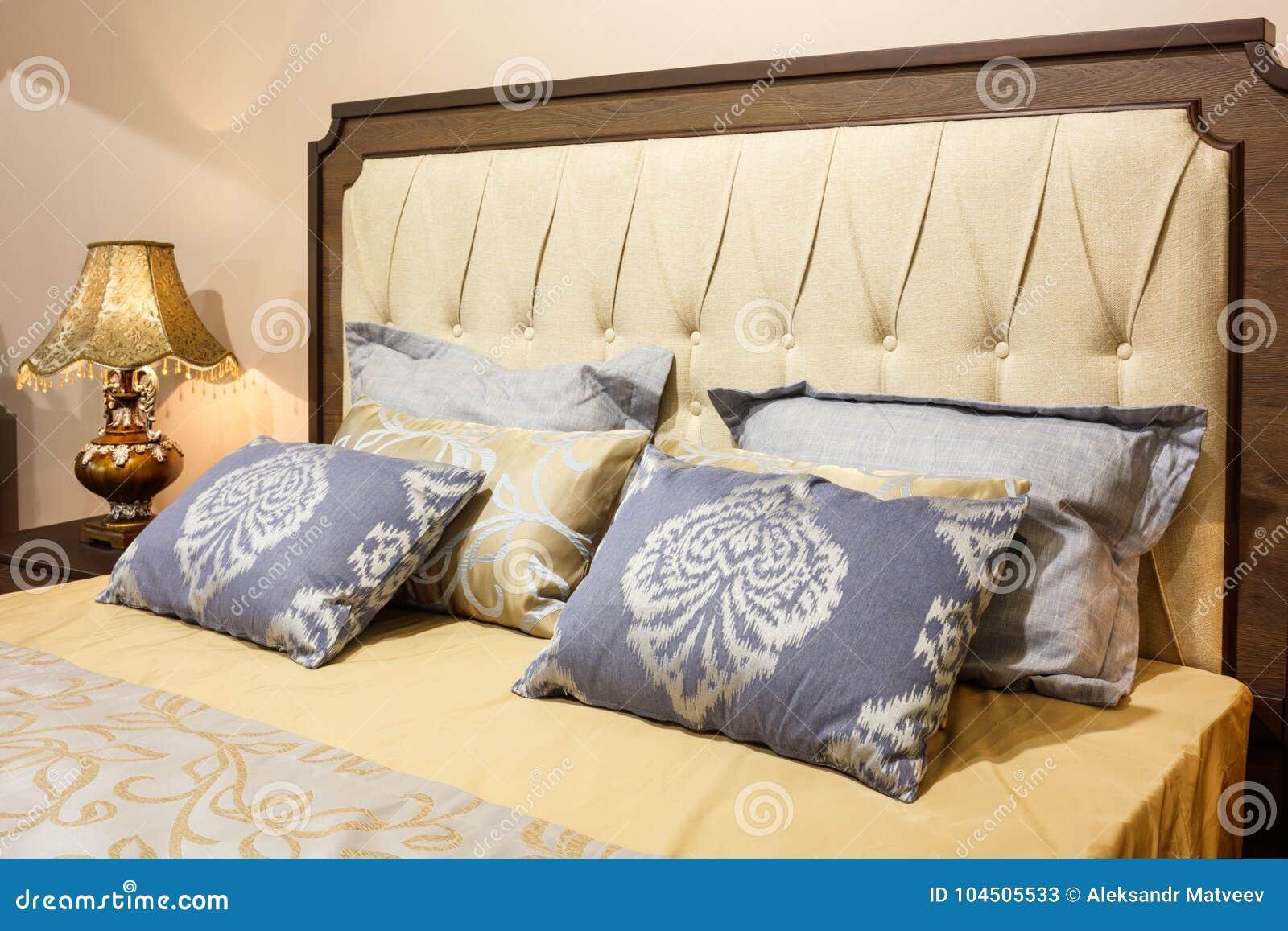 Quarto moderno luxuoso do estilo nos tons amarelos e azuis, interior de um quarto do hotel, coxins com um ornamento do teste padr