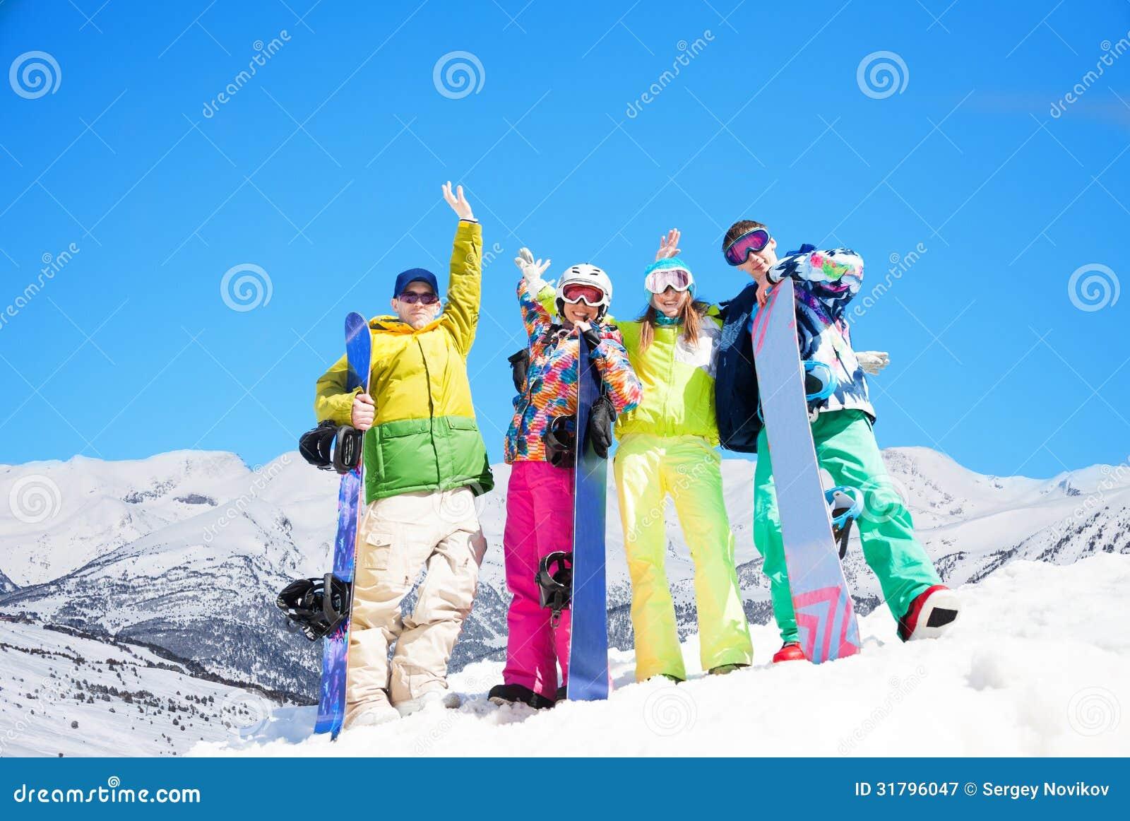 Quatre amis heureux avec des surfs des neiges