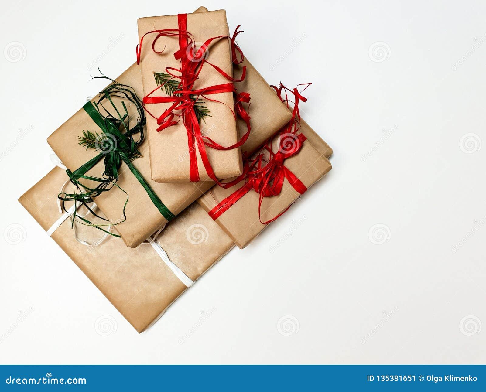 Quatre boîte-cadeau de Noël ouvrés et rouges et rubans verts sur un fond blanc
