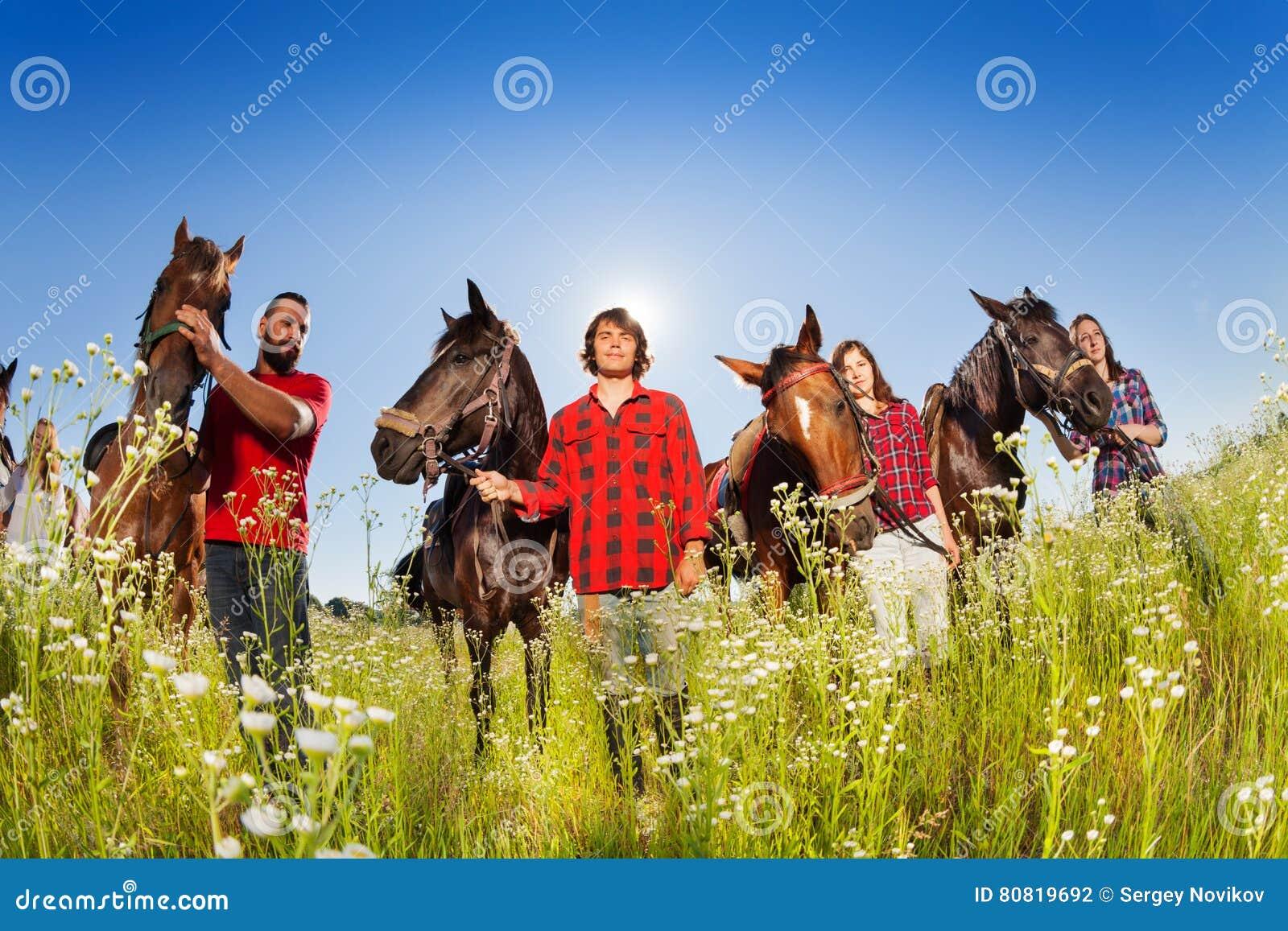 Quatre cavaliers heureux marchant avec leurs chevaux