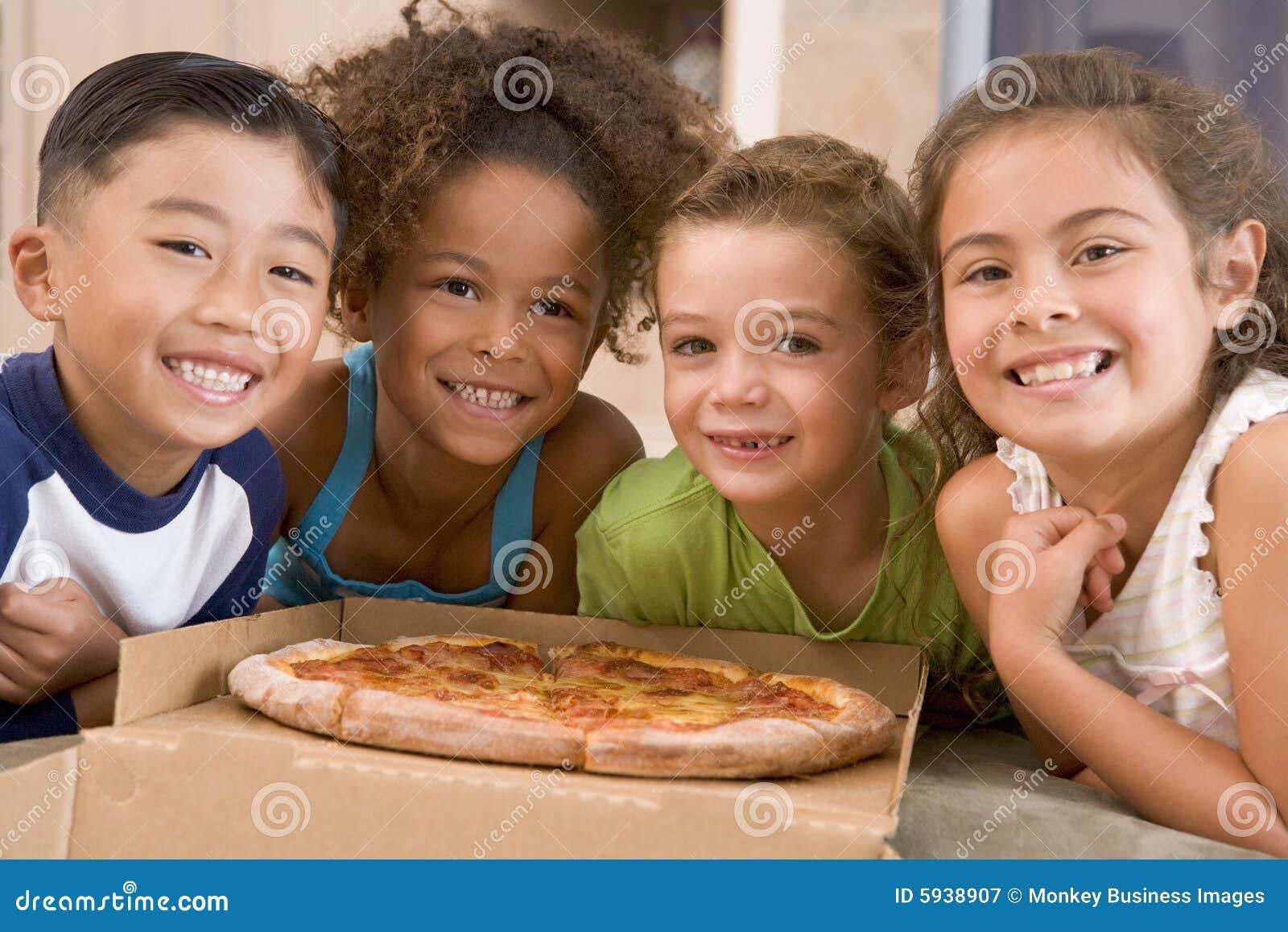 Quatre enfants en bas âge à l intérieur avec le sourire de pizza