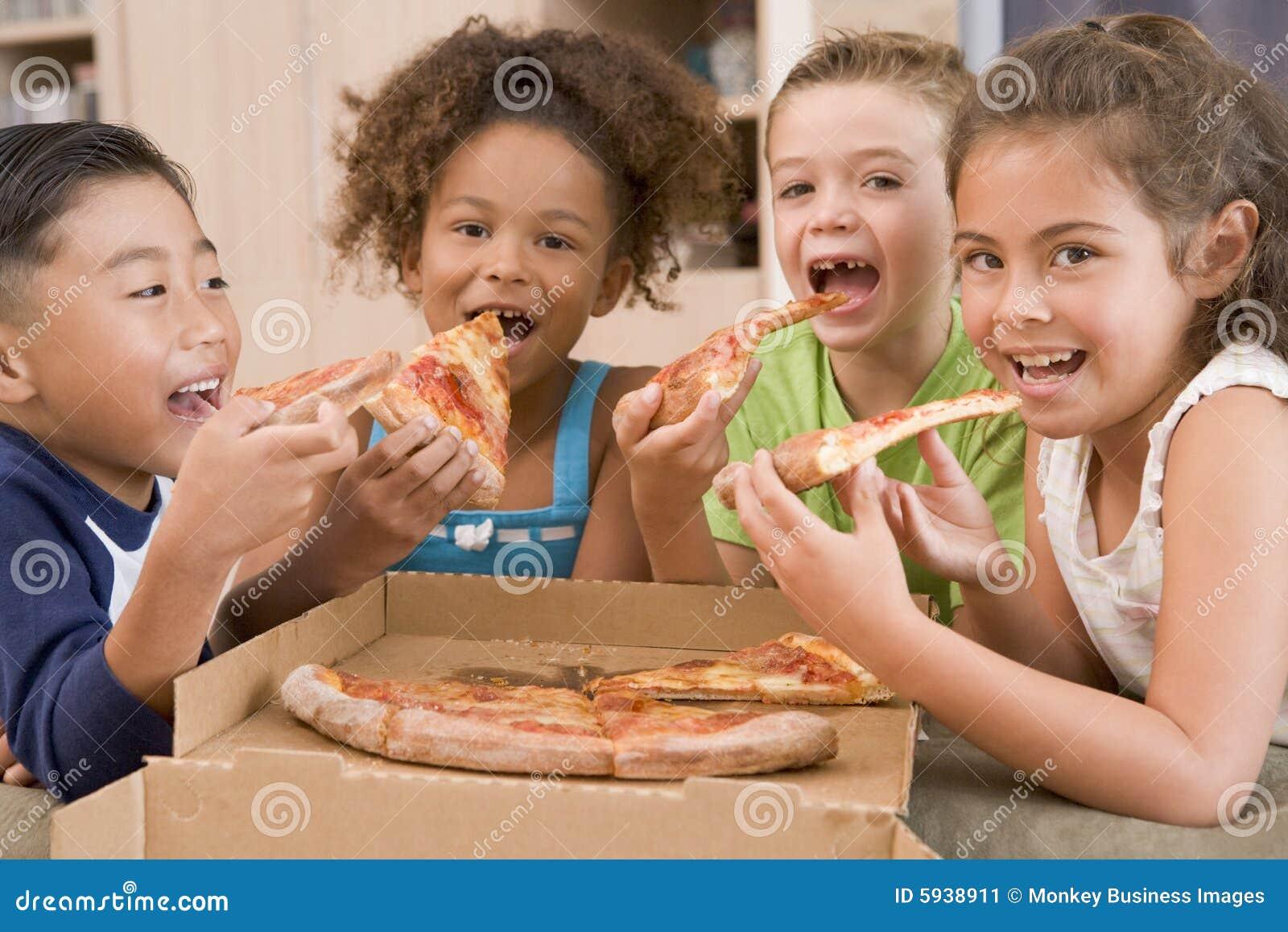 Quatre enfants en bas âge mangeant à l intérieur de la pizza