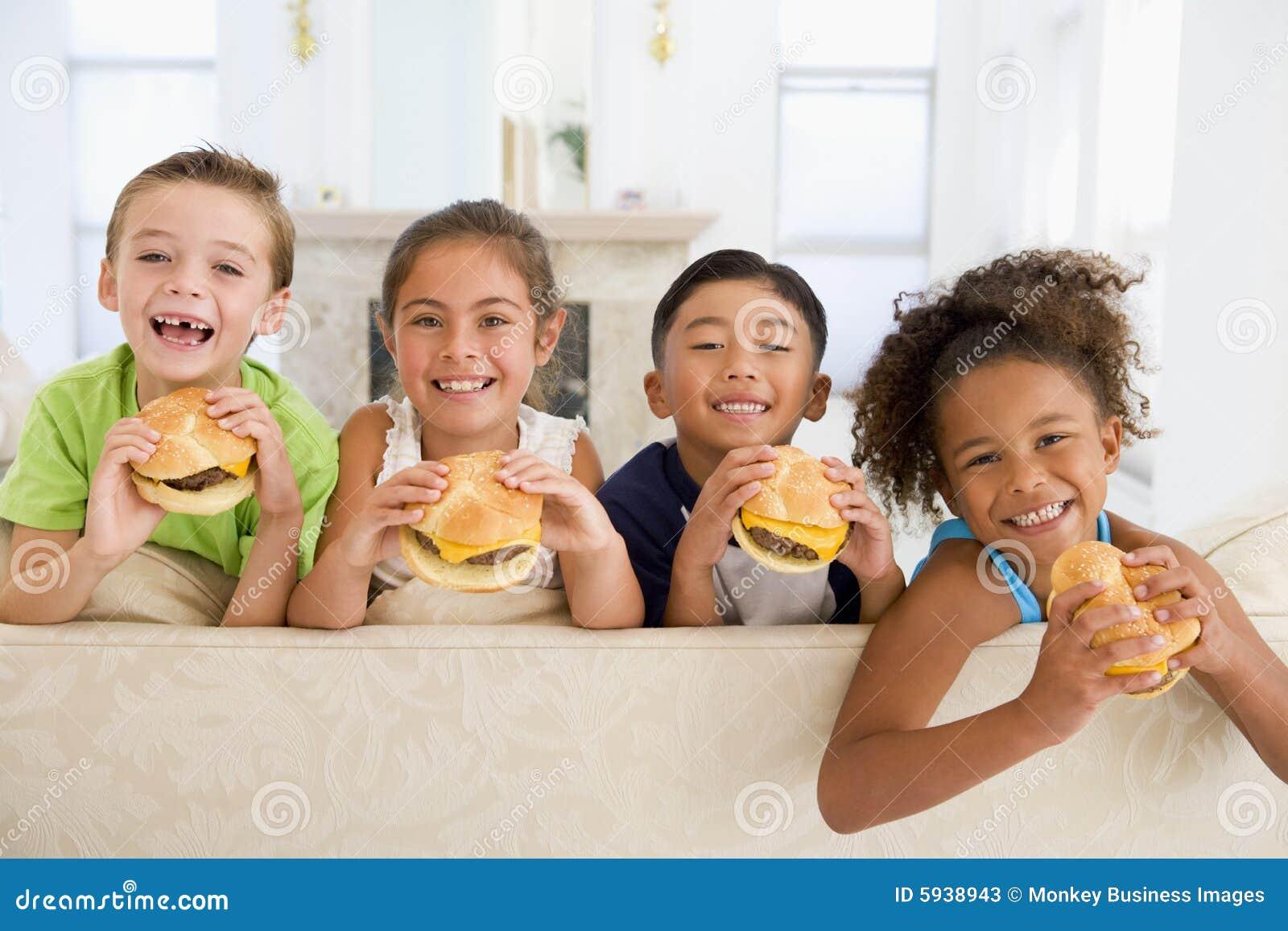 Quatre enfants en bas âge mangeant des cheeseburgers
