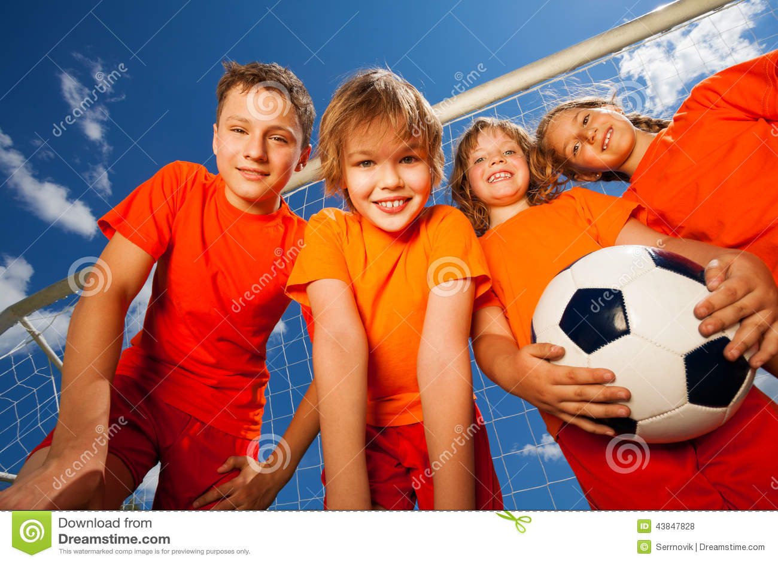 Quatre enfants heureux avec le portrait du football