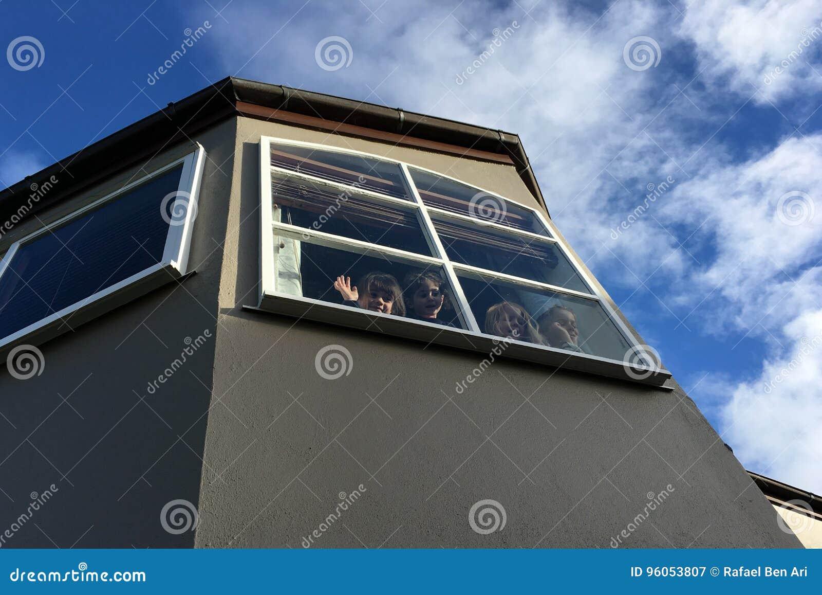 Quatre enfants ondulant au revoir d une fenêtre
