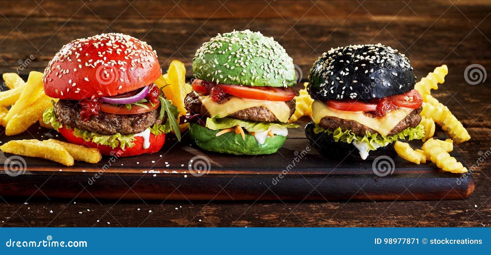 Quatre hamburgers de boeuf sur les petits pains colorés