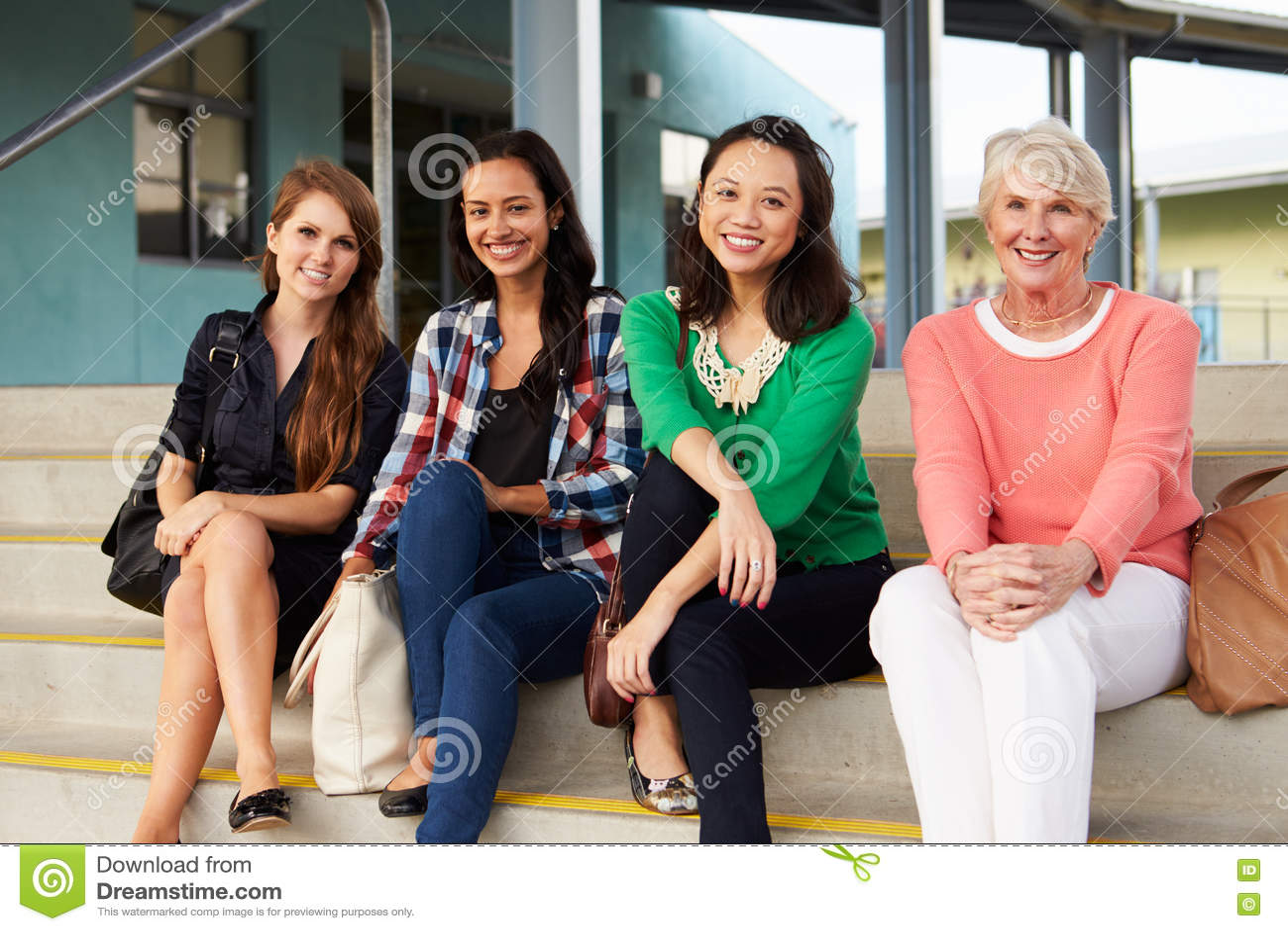Quatre professeurs féminins s asseyant sur des étapes à l entrée de l école