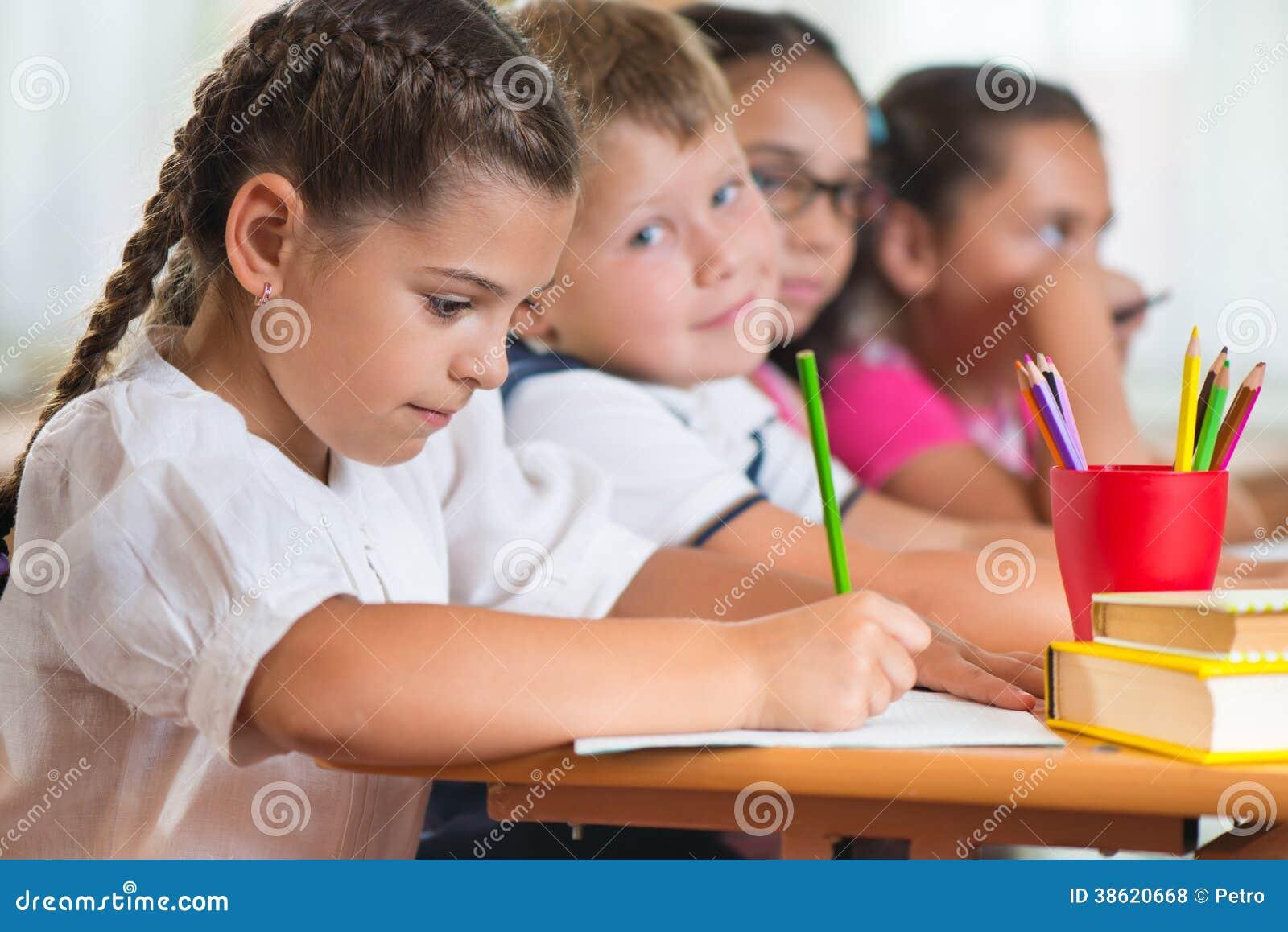 Quatro alunos diligentes que estudam na sala de aula