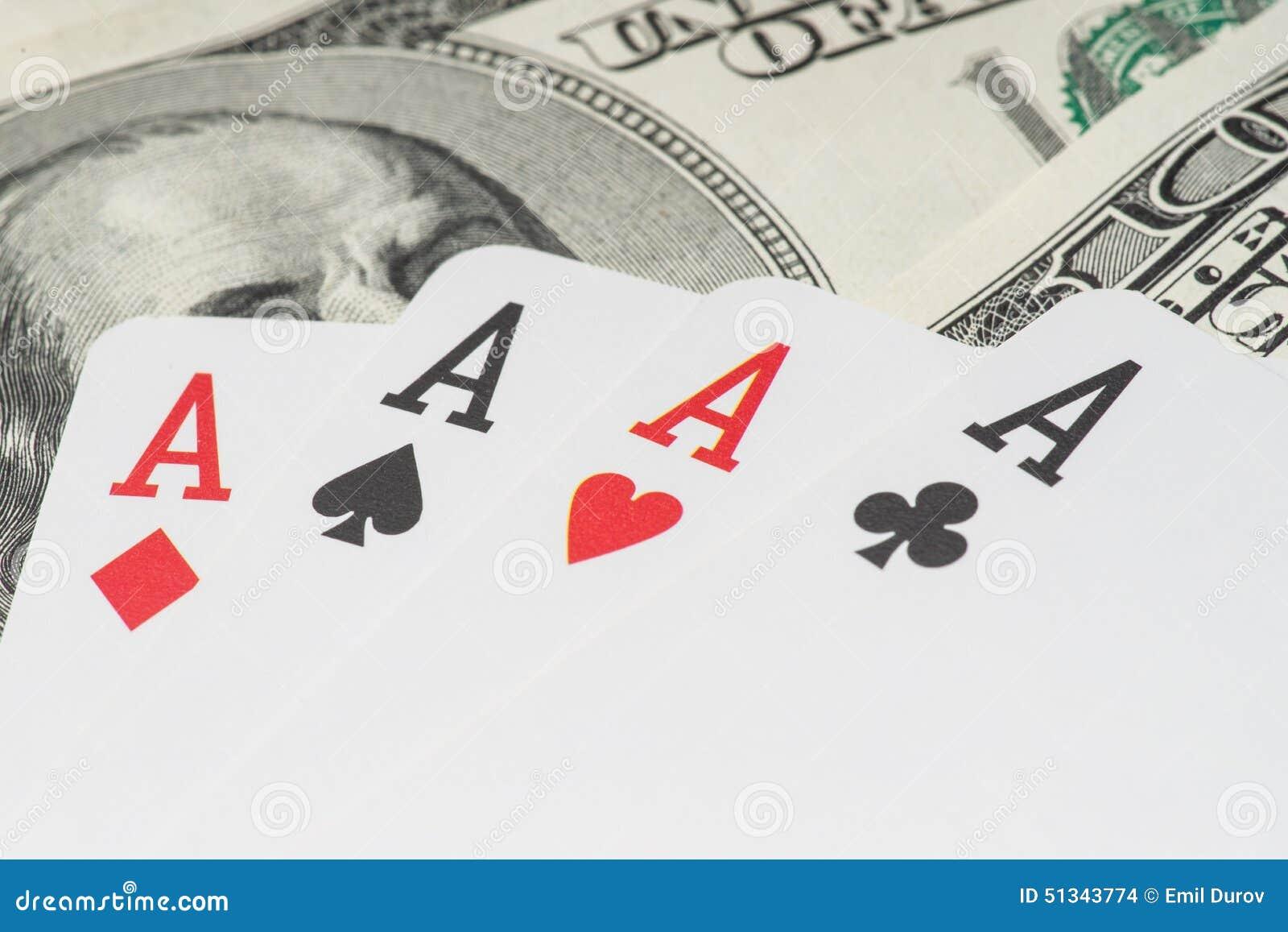 Quatro cartões de jogo do pôquer dos áss entre U S Dólares