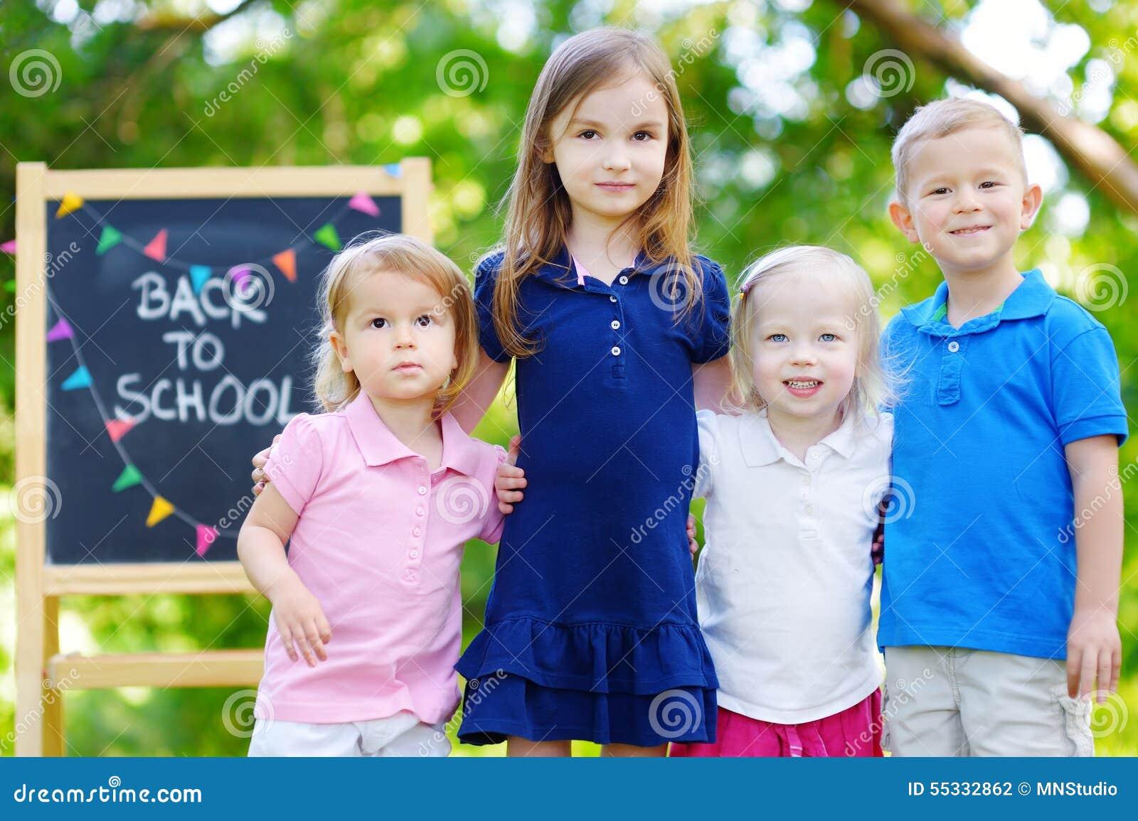 Quatro crianças adoráveis estão indo para trás à escola