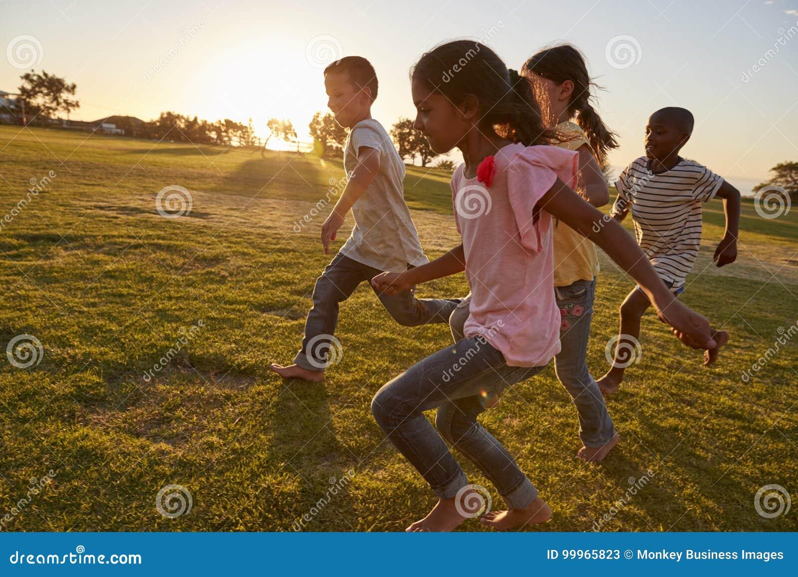 Quatro crianças que correm com os pés descalços em um parque