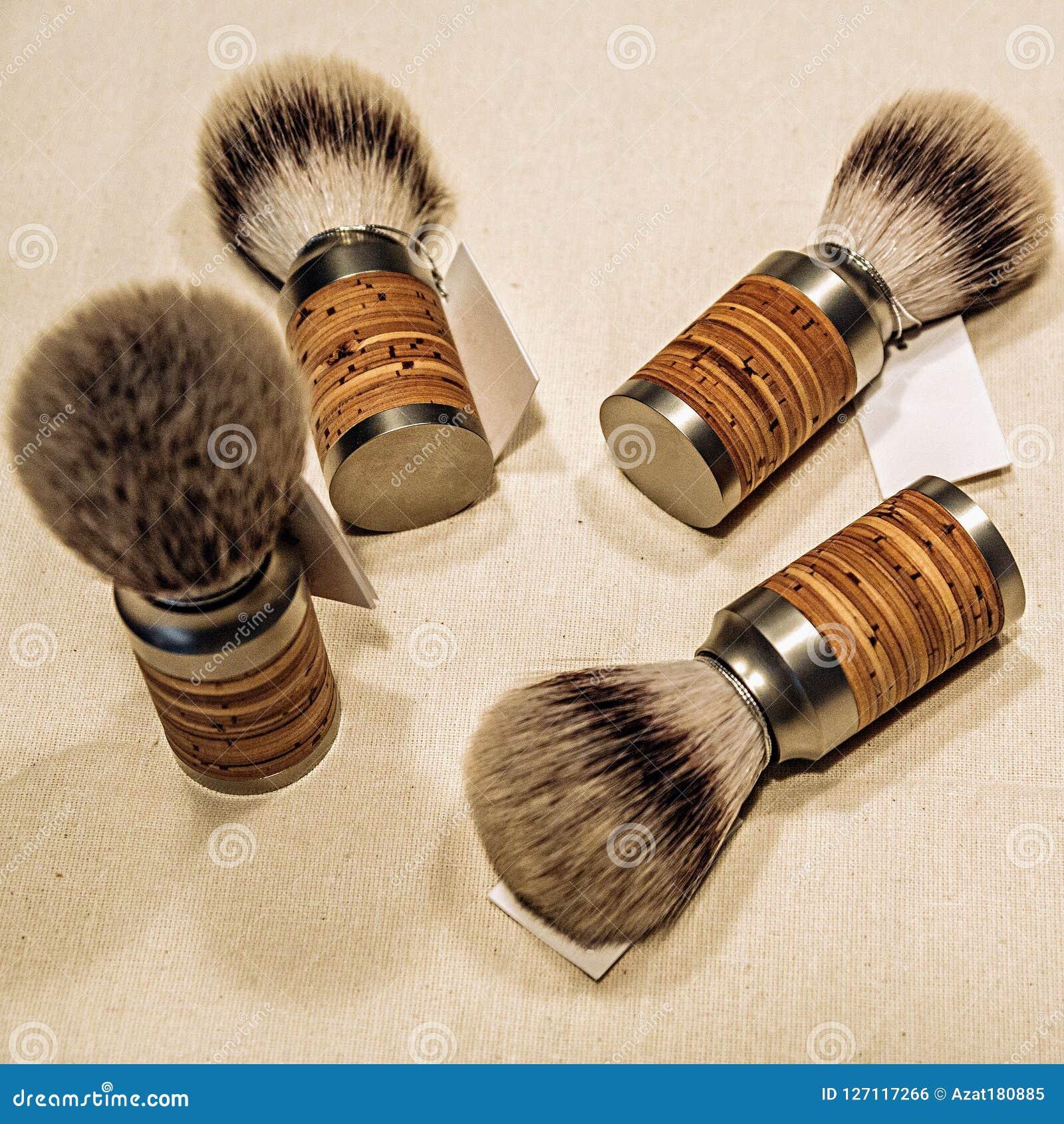 Quatro escovas de rapagem de madeira na lona
