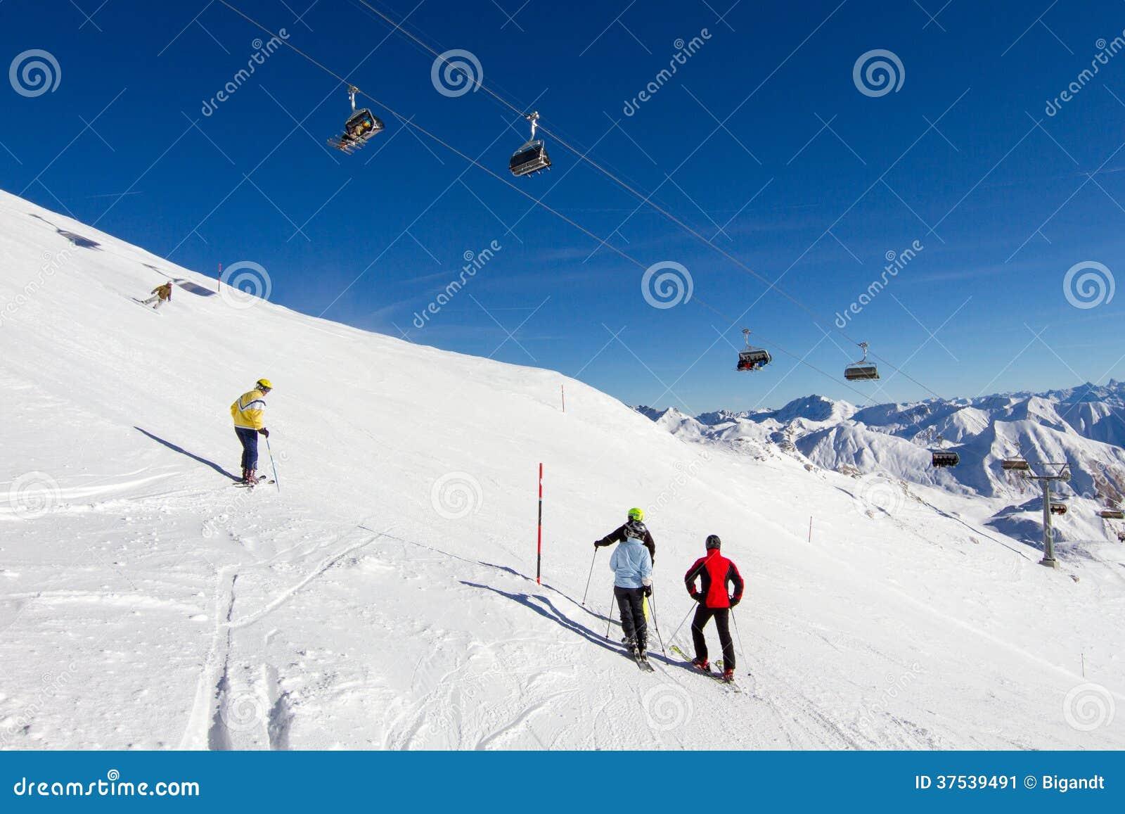 Quatro esquiadores na inclinação do esqui